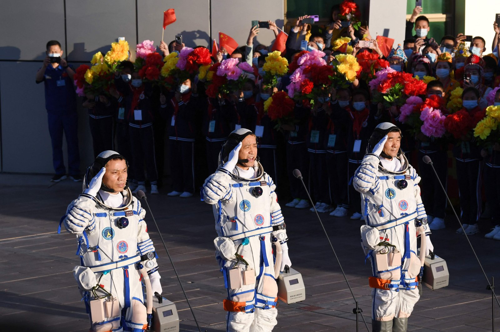 Astronauts Nie Haisheng (C), Liu Boming (R) and Tang Hongbo salute during a departure ceremony before boarding the Shenzhou-12 spacecraft on a Long March-2F carrier rocket at the Jiuquan Satellite Launch Center in the Gobi desert, northwest China, June 17, 2021. (AFP Photo)
