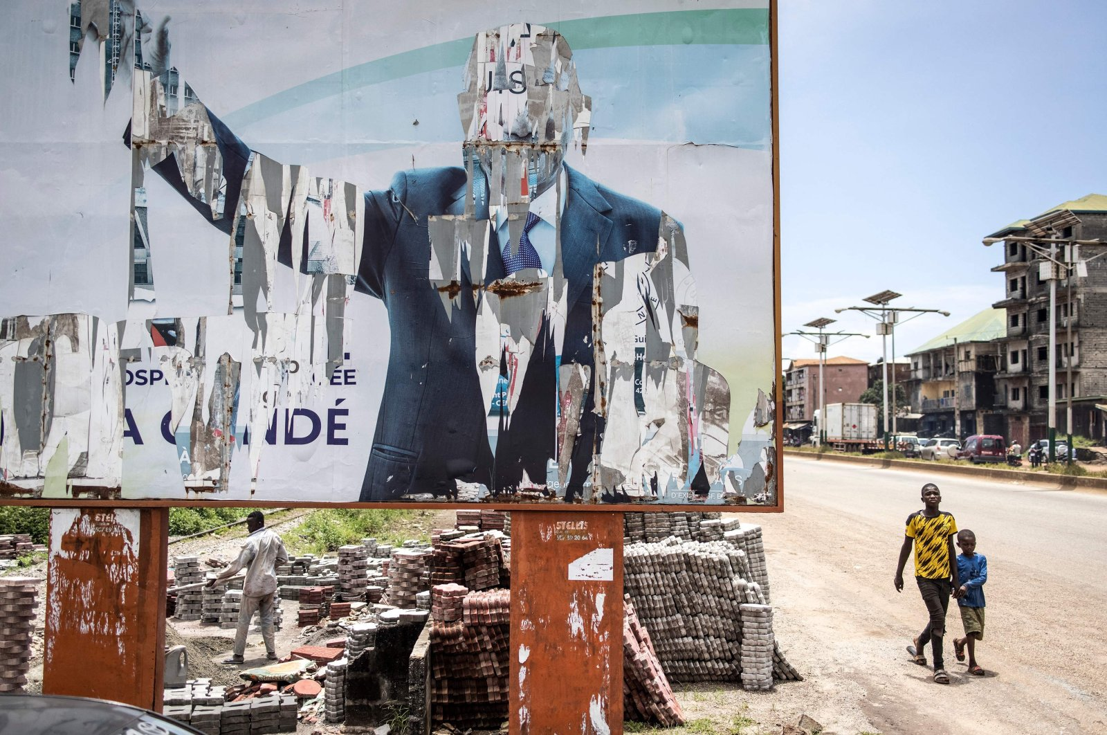 Two young boys walk past a torn billboard of the former president of Guinea, Alpha Conde, in Conakry, Guinea, Sept. 16, 2021. (AFP Photo)