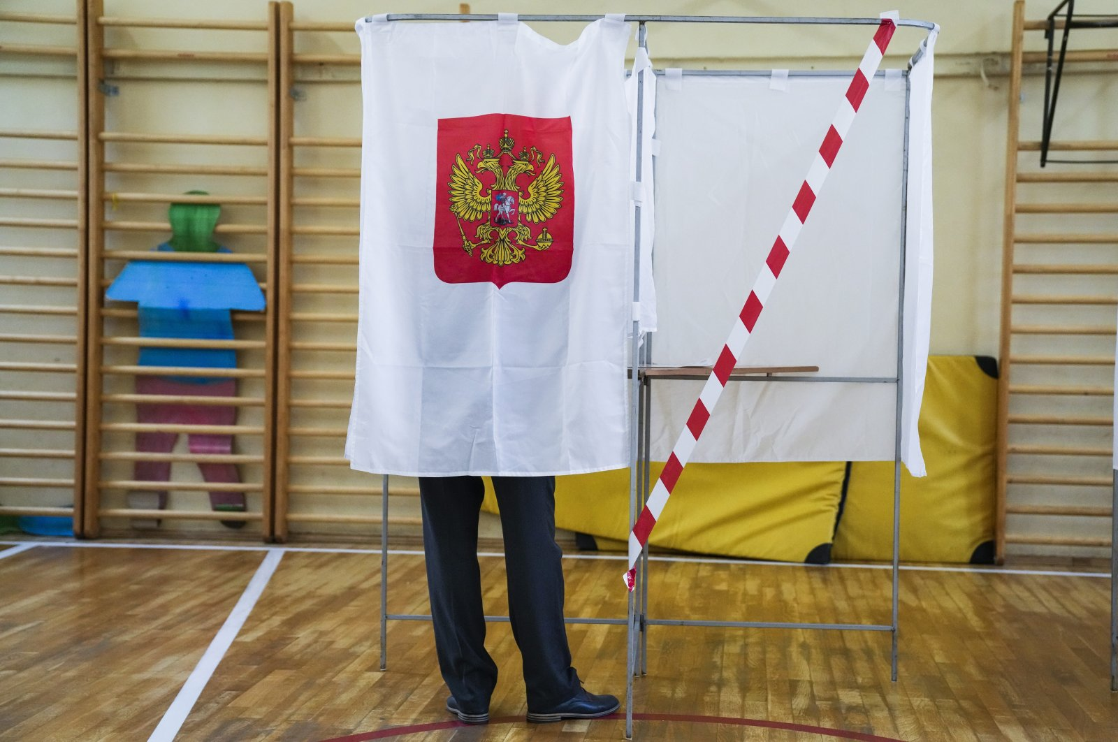 A man fills out his ballot in a voting booth during the parliamentary elections in Moscow, Russia, Sept. 17, 2021. (AP Photo)