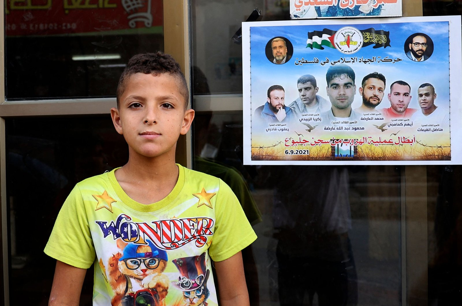A Palestinian child looks on while standing next to a poster expressing solidarity with the six Palestinian prisoners who escaped from Israel's Gilboa prison, hanging outside a shop at the Jenin camp for Palestinian refugees in the north of the occupied West Bank, Palestine, Sept. 12, 2021. (AFP Photo)