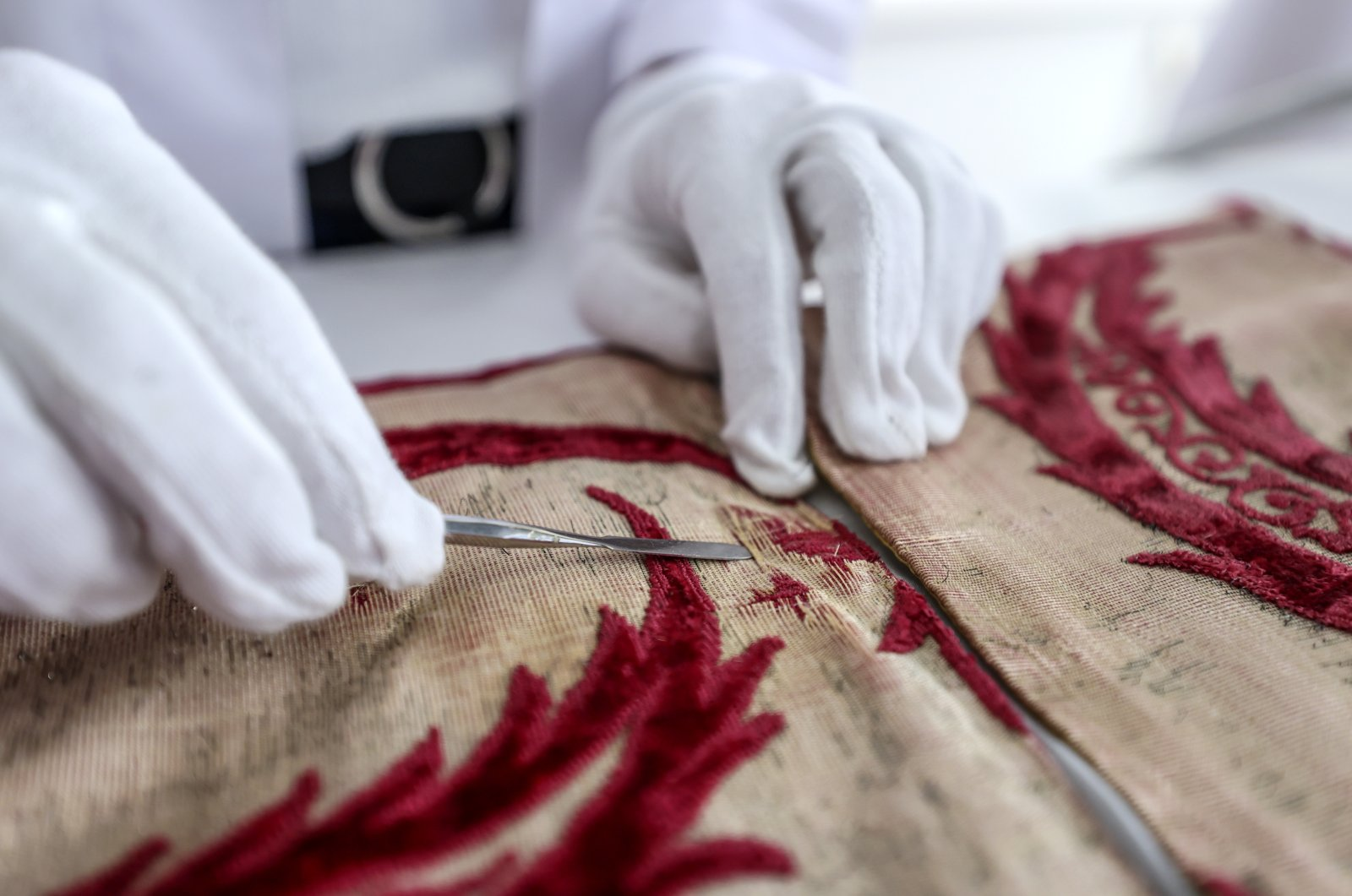 A close-up of a hand of a restorer while working on Sultan Suleiman I's caftan at the National Palaces Textile Workshop, Istanbul, Turkey, Sept. 16, 2021. (AA Photo)