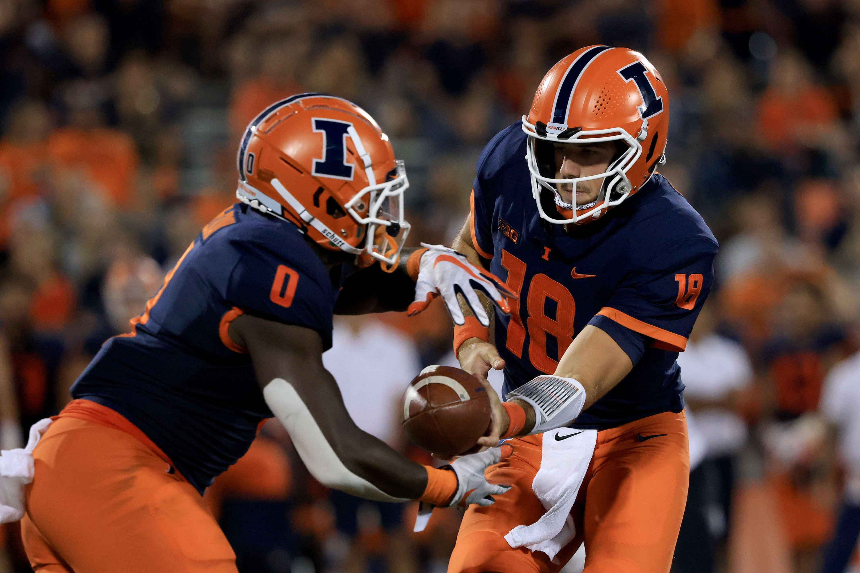 Brandon Peters (18) hands the ball off to Josh McCray (0) of the Illinois Fighting Illini during the first quarter in the game against the Maryland Terrapins at Memorial Stadium, Champaign, Illinois, U.S., Sept. 17, 2021. (AFP Photo)