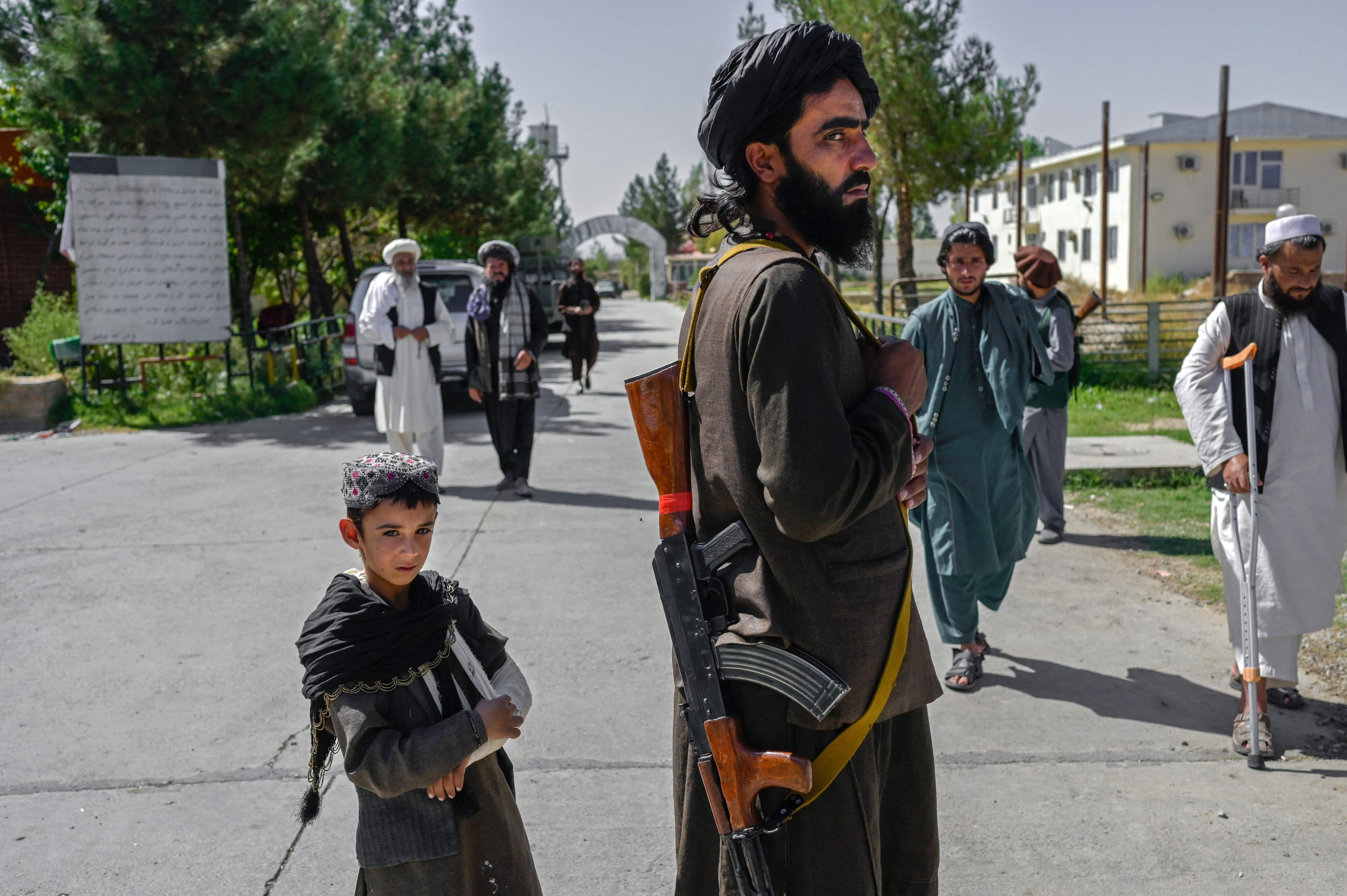 An Afghan boy stands next to a member of the Taliban in front of the Pul-e-Charkhi prison in Kabul, Afghanistan, Sept. 16, 2021. (Photo by BULENT KILIC via AFP)