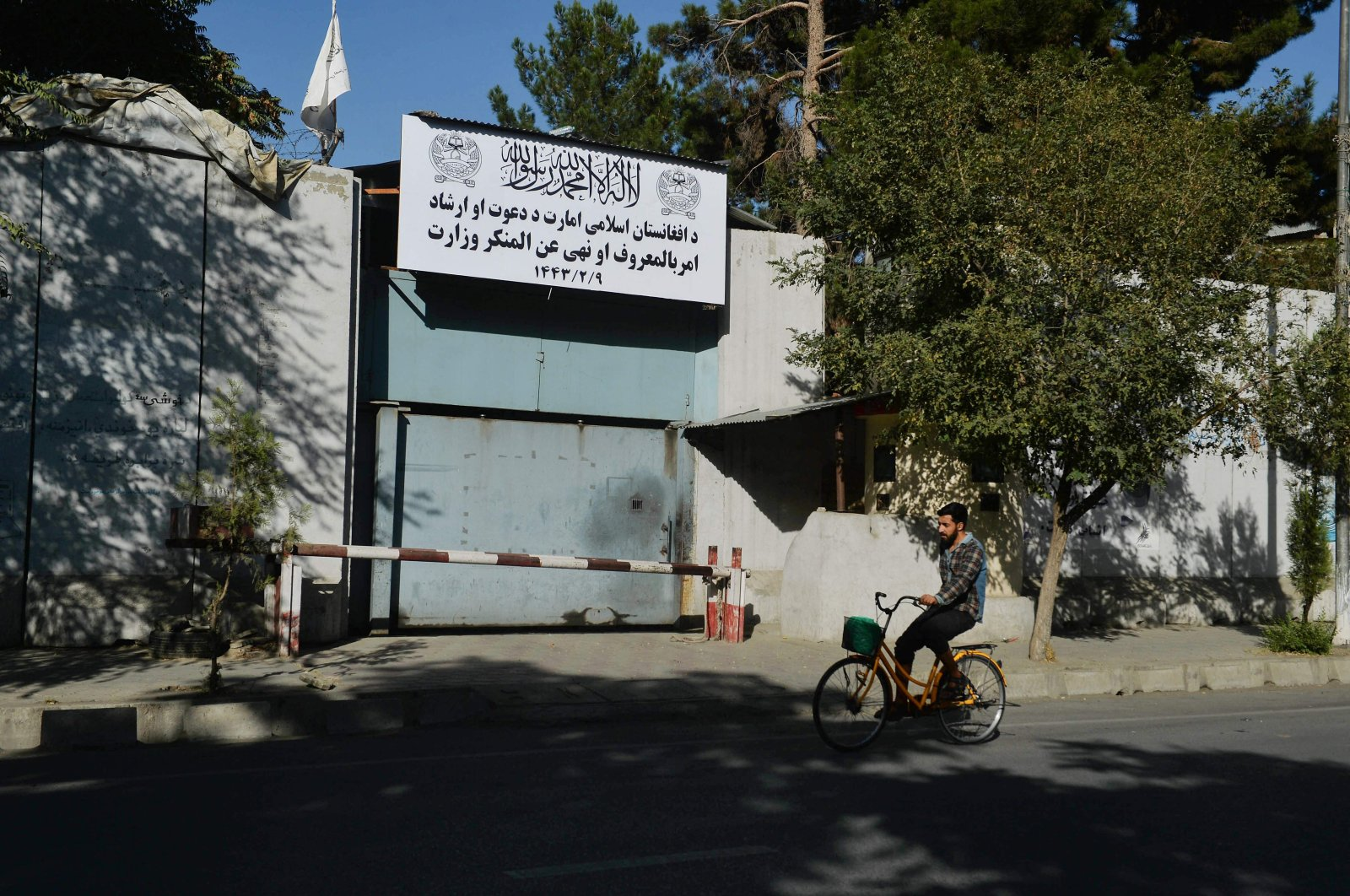 A man rides his bike past an entrance gate of the Ministry for the Promotion of Virtue and Prevention of Vice in Kabul, Afghanistan, Sept. 17, 2021. (Photo by Hoshang Hashimi via AFP)