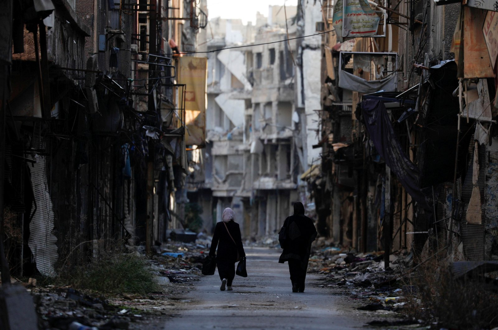 This file photo shows women walking past damaged buildings at the Yarmouk Palestinian refugee camp on the southern outskirts of Damascus, Syria, Dec. 1, 2020. (Reuters Photo)