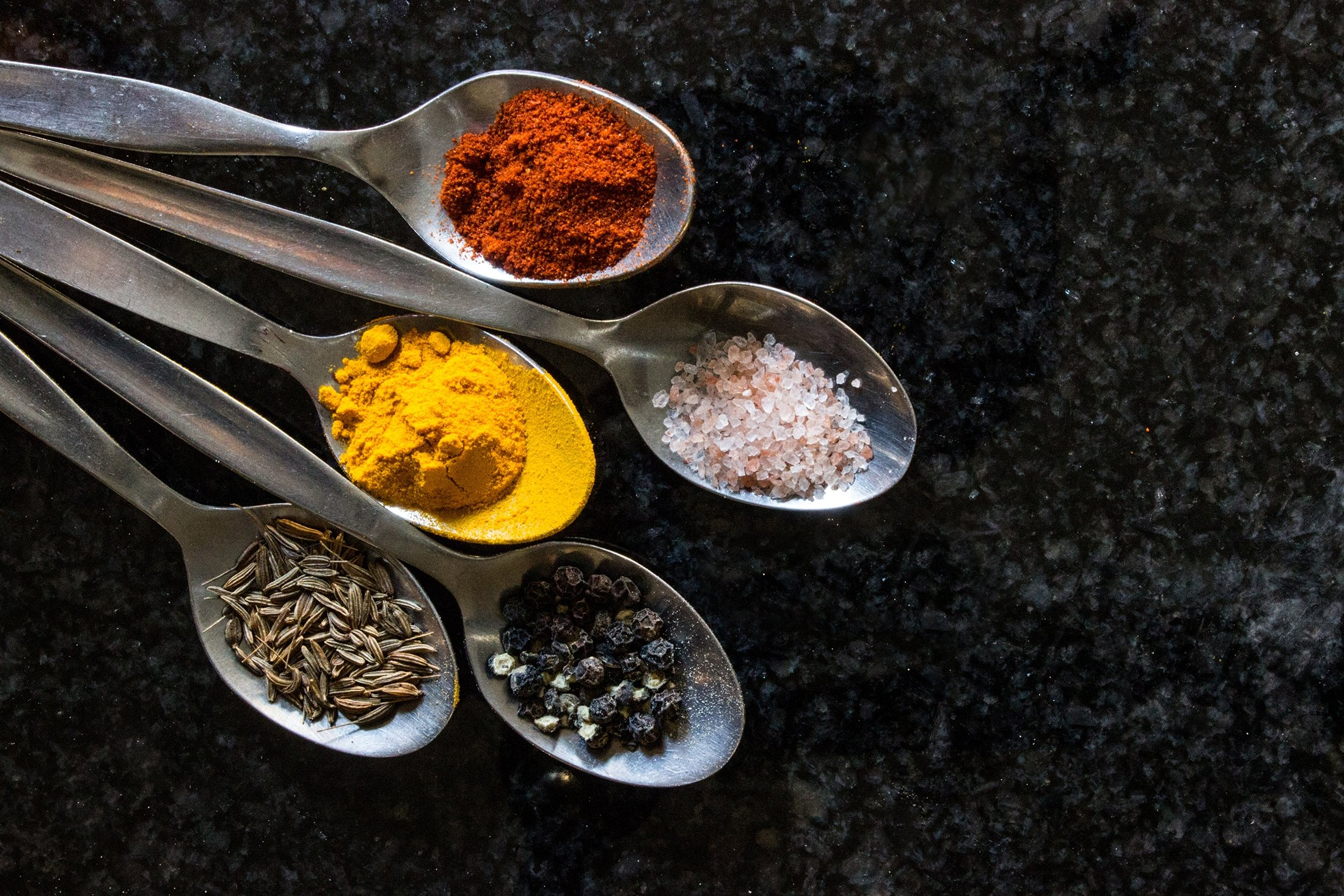 Five Turkish teaspoons filled with various types of spices, namely salt, pepper, cumin, turmeric and curry powder. (Shutterstock Photo)