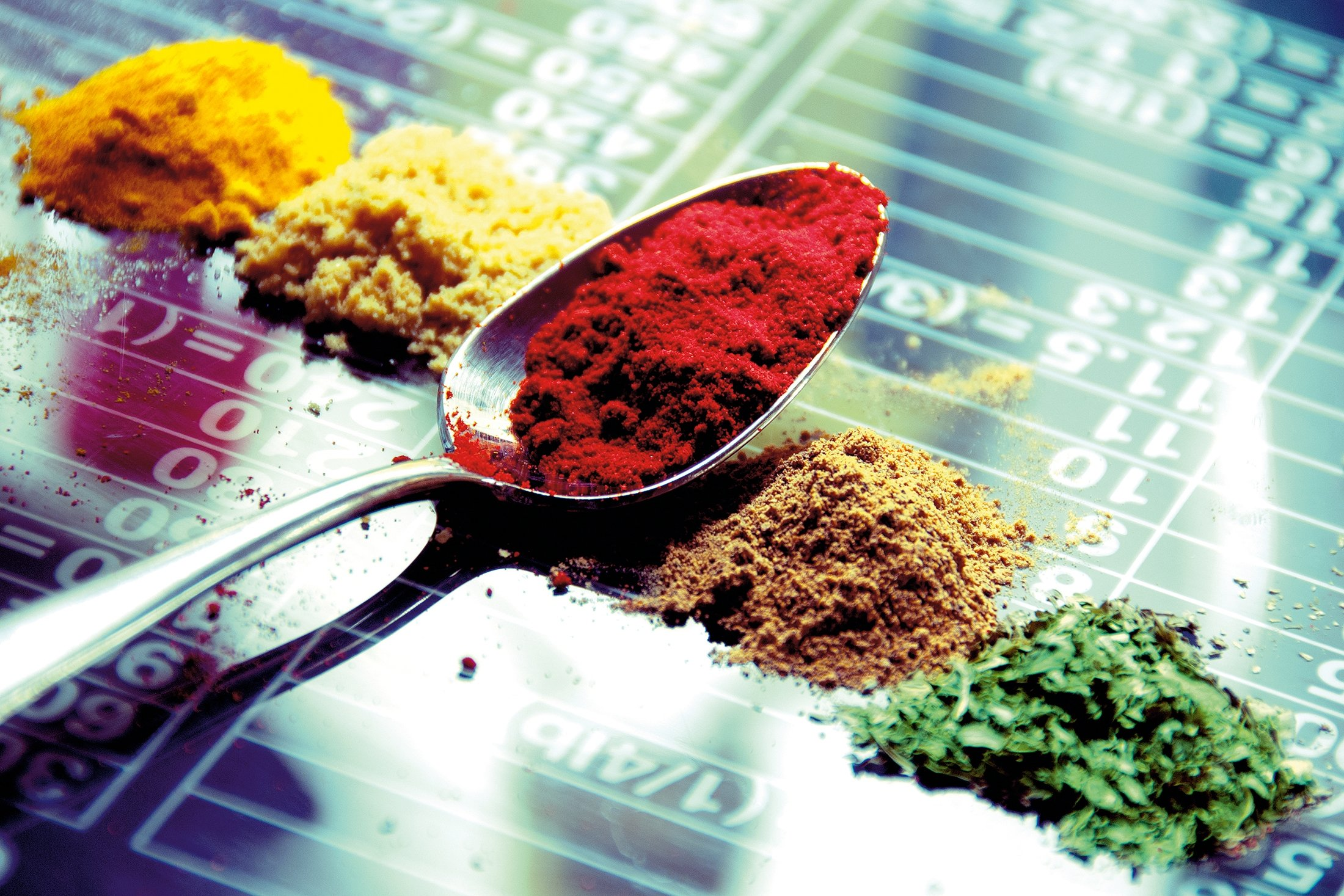 A teaspoon alongside mounds of spices. (Getty Images)