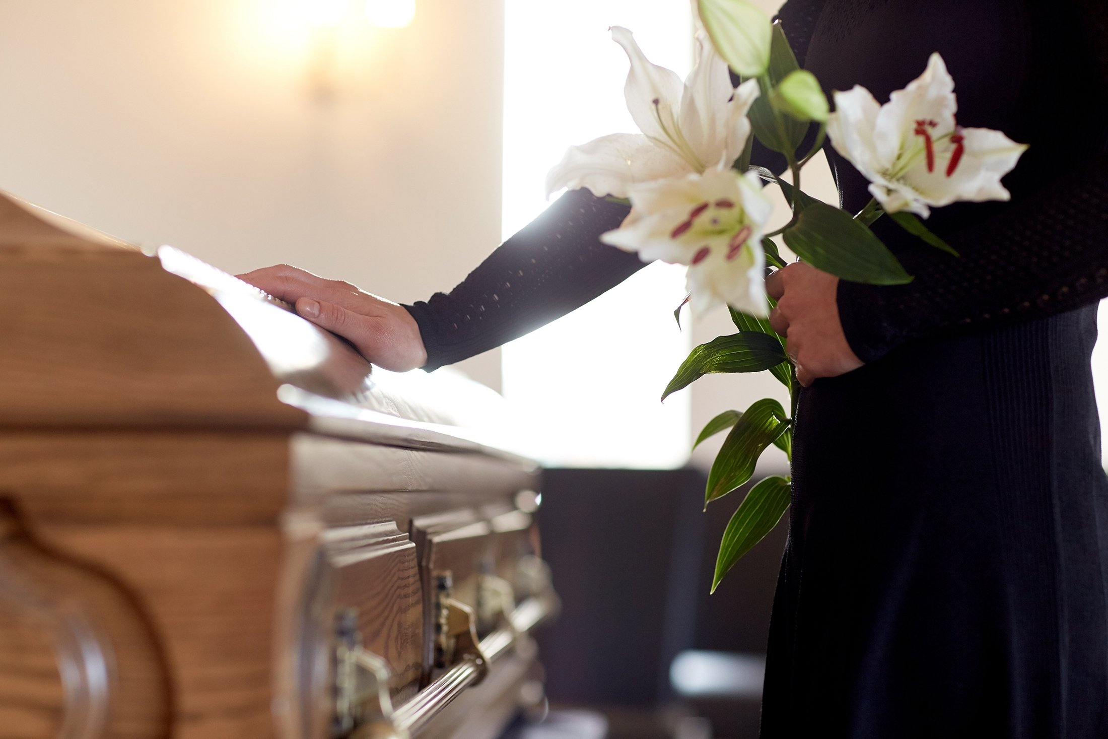 A woman with white lilies beside a coffin at a funeral in a church. (Shutterstock Photo)