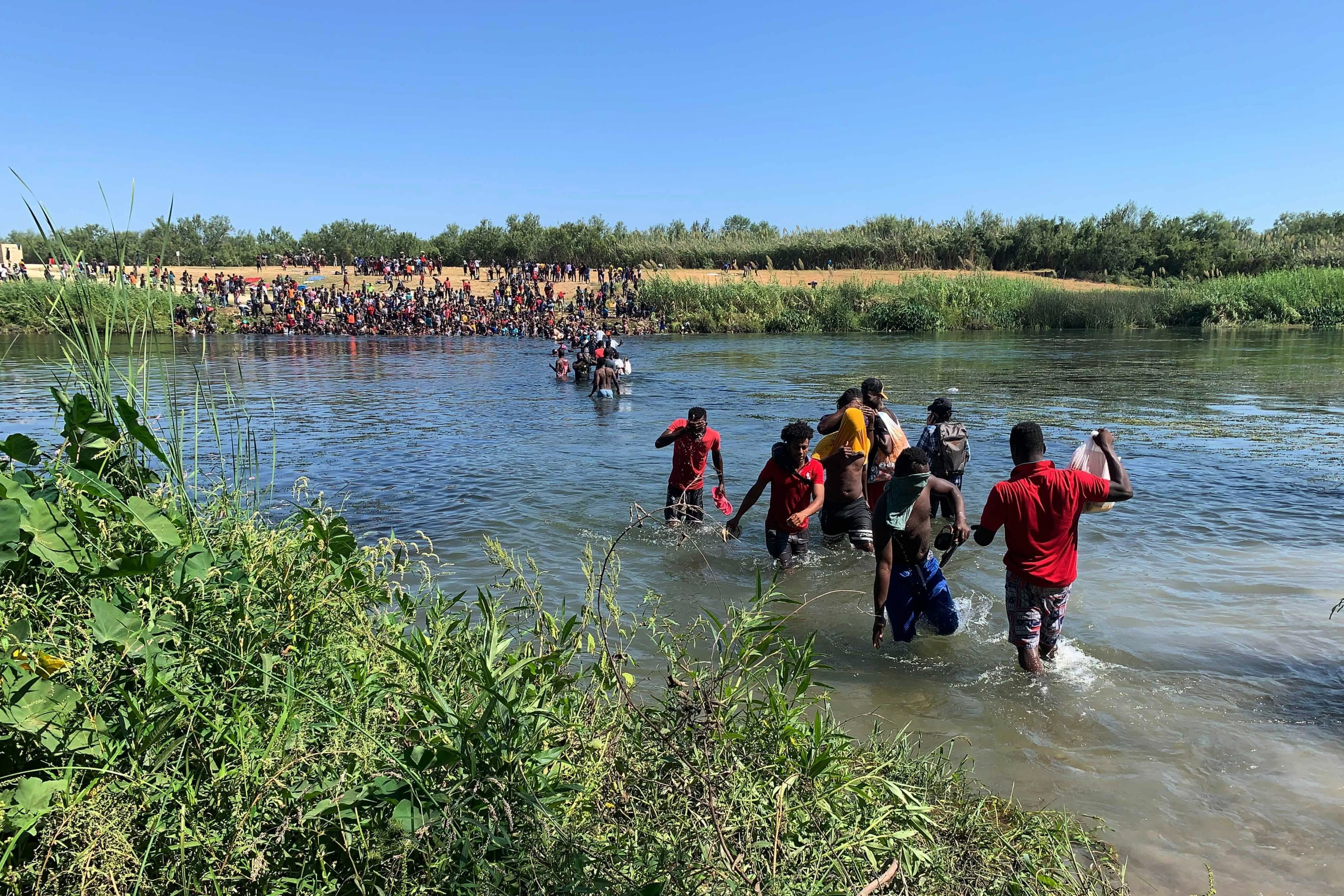 Migrants find an alternate place to cross from Mexico to the United States after access to a dam was closed, Ciudad Acuña, Mexico, Sept. 19, 2021. (AP Photo)