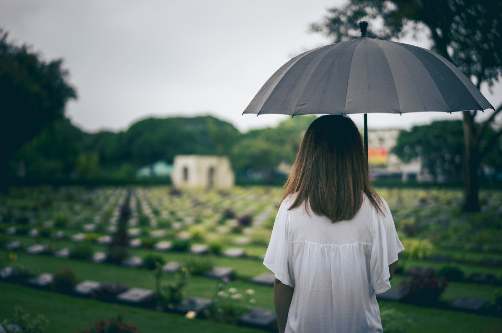 A young woman holds a black umbrella while mourning at a cemetery. (Shutterstock Photo)