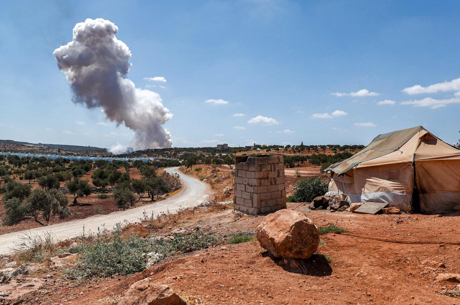 A plume of smoke rises after an aerial bombardment near a make-shift camp for displaced Syrians near the town of Kafraya in the north of Syria's rebel-held Idlib province, Sept. 7, 2021. (Photo by OMAR HAJ KADOUR / AFP)