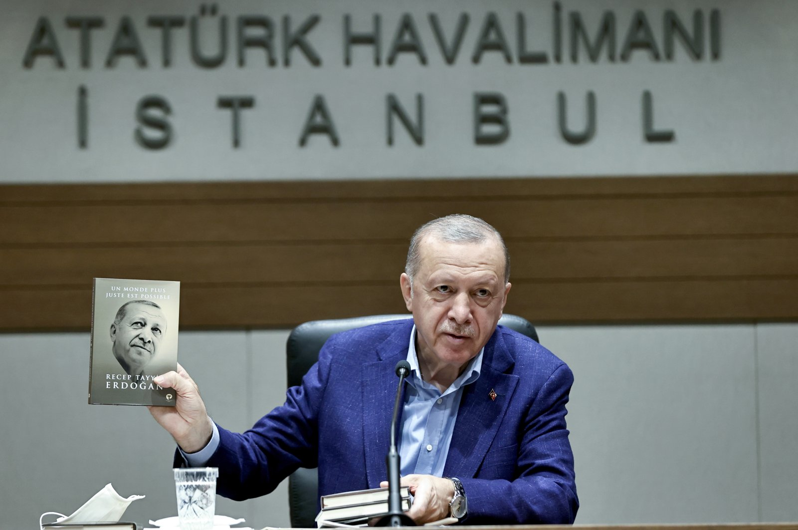 """President Recep Tayyip Erdoğan holds his book """"A Fairer World Is Possible"""" while addressing reporters ahead of his visit to the United States, Istanbul, Turkey, Sept. 19, 2021. (AA Photo)"""