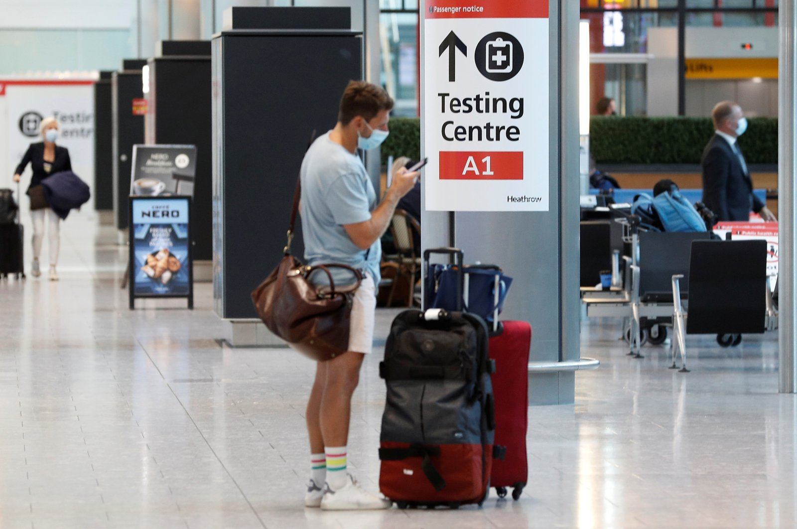 A passenger stands next to a COVID-19 testing center sign in the international arrivals area of Terminal 5 in London's Heathrow Airport, Britain, Aug. 2, 2021. (Reuters Photo)