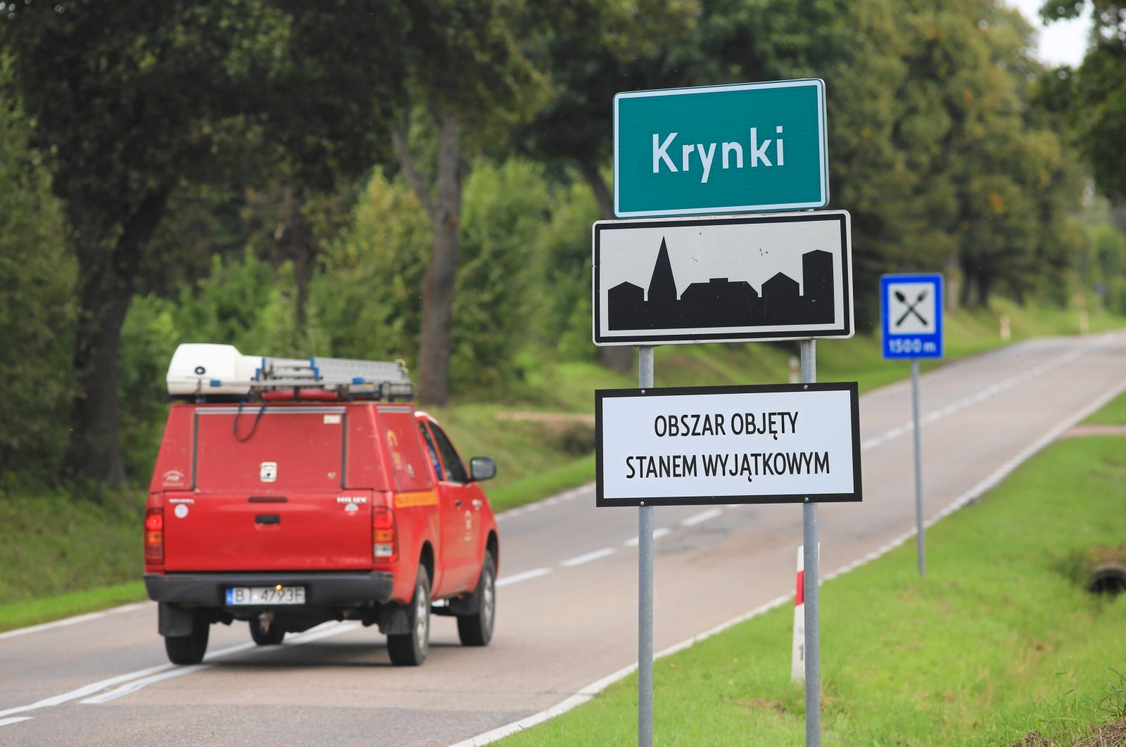 """Road sign reading """"Area in state of emergency"""" after declaring a state of emergency on Belarus border amid migrant surge is seen in Krynki, Poland, Sept. 3, 2021. (Reuters File Photo)"""