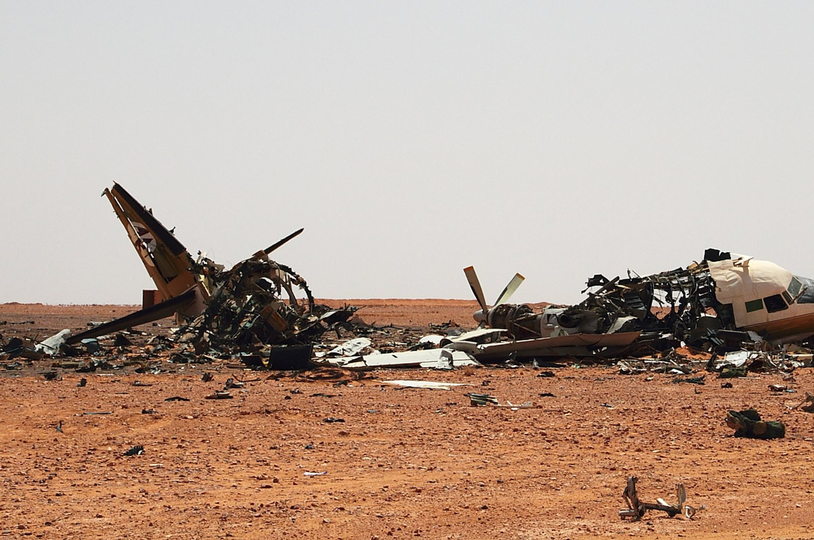 The wreckage of a plane is scattered in the desert outside a military base approximately 45 kilometers outside of Bani Walid, Libya, Saturday, Sept. 3, 2011. (AP File Photo)