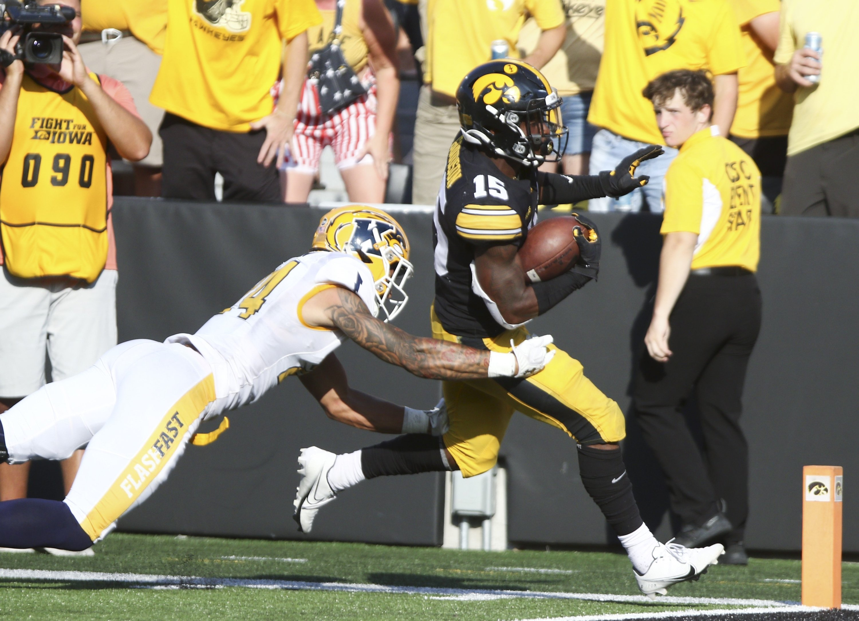 Running back Tyler Goodson (15) of the Iowa Hawkeyes runs in a touchdown during the second half in front of safety Nico Bolden (24) of the Kent State Golden Flashes at Kinnick Stadium, Iowa City, Iowa, U.S., Sept. 18, 2021. (AFP Photo)