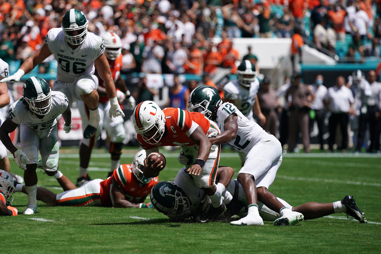 Michigan State Spartans cornerback Chester Kimbrough (12) tackles Miami Hurricanes quarterback D'Eriq King (1) during the first half at Hard Rock Stadium, Miami Gardens, Florida, U.S., Sept. 18, 2021. (Jasen Vinlove-USA TODAY Sports via Reuters)