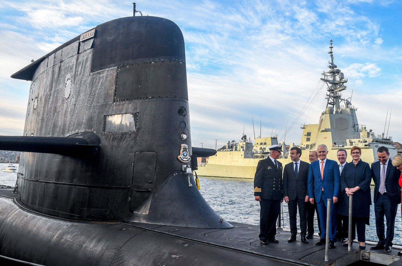 A file photo shows French President Emmanuel Macron (2L) and Australian Prime Minister Malcolm Turnbull (C) standing on the deck of HMAS Waller, a Collins-class submarine operated by the Royal Australian Navy, at Garden Island in Sydney, Australia, May 2, 2018. (AFP Photo)