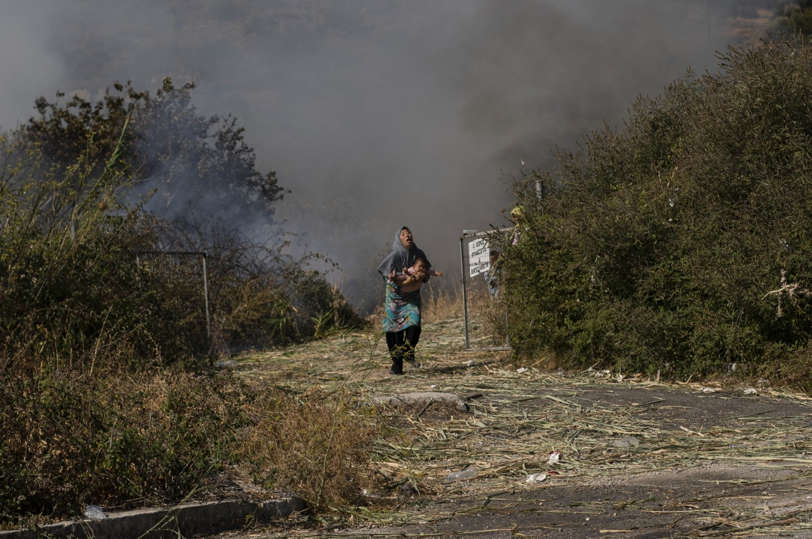 An Afghan woman from the destroyed Moria camp holds her baby as she runs to avoid a small fire in a field near where refugees and migrants are sheltered, in Lesbos island, Greece, Sept. 12, 2020. (AP Photo)