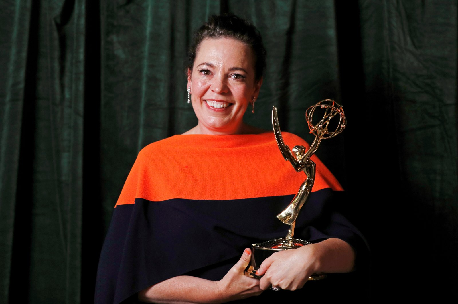 """Olivia Colman poses with her Emmy award for Outstanding Lead Actress in a Drama Series, backstage at the Netflix UK Primetime Emmy for """"The Crown"""", in London, Britain, Sept. 20, 2021. (REUTERS Photo)"""