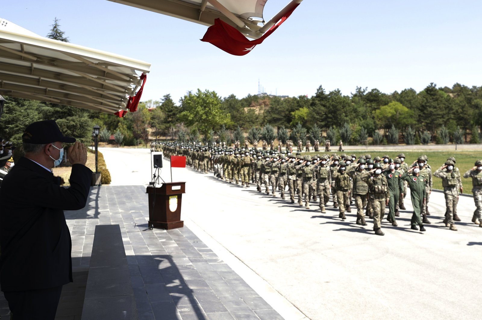 Defense Minister Hulusi Akar salutes Turkish troops who were operating Kabul Hamid Karzai International Airport in Afghanistan, during a ceremony at Ankara Esenboğa Airport, Turkey, Aug. 28, 2021. (AP File Photo)