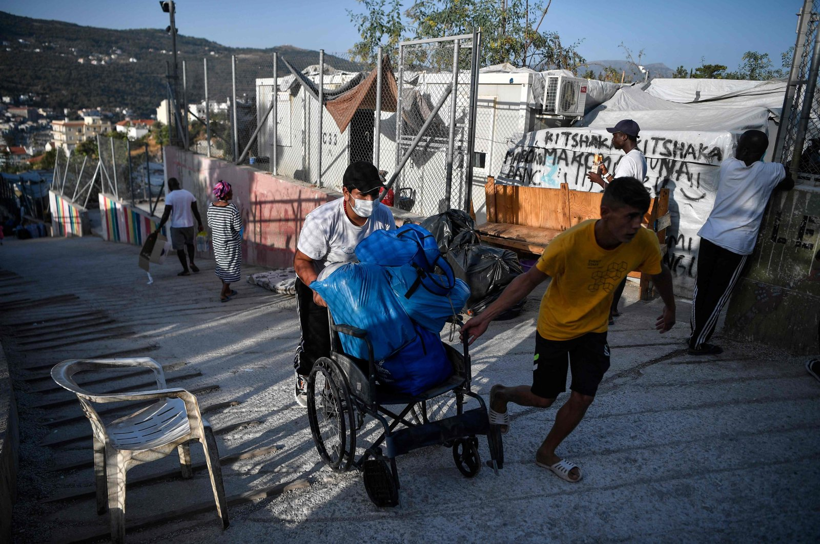 """Men carry belongings on a cart at the old Vathy camp, on the island of Samos before being transferred to the new Samos RIC, the first of five new """"closed"""" migrant camps, Greece, Sept. 20, 2021 (AFP Photo)"""