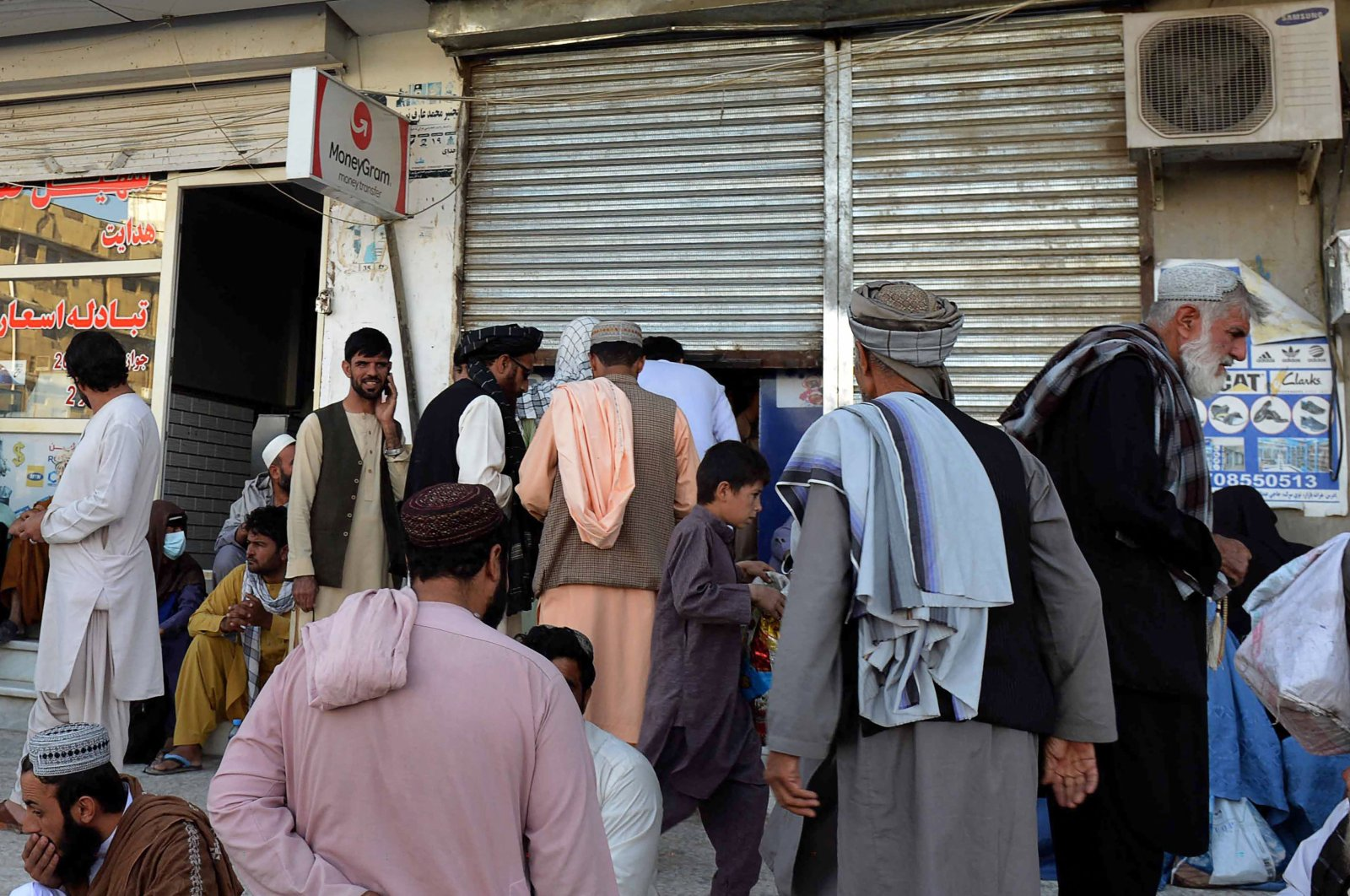 People sit outside a bank as they wait to withdraw money in Kandahar on September 20, 2021. (AFP Photo)