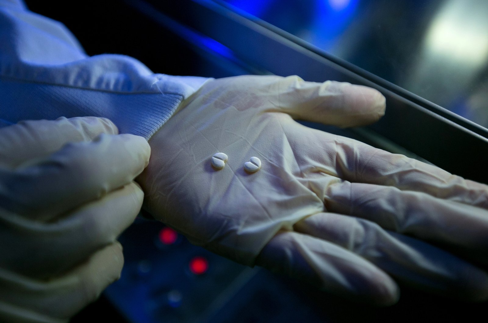 A laboratory technician holds blood pressure tablets during quality checks in the laboratories at the Merck headquarters in Darmstadt, Germany, June 25, 2014. (Getty Images)