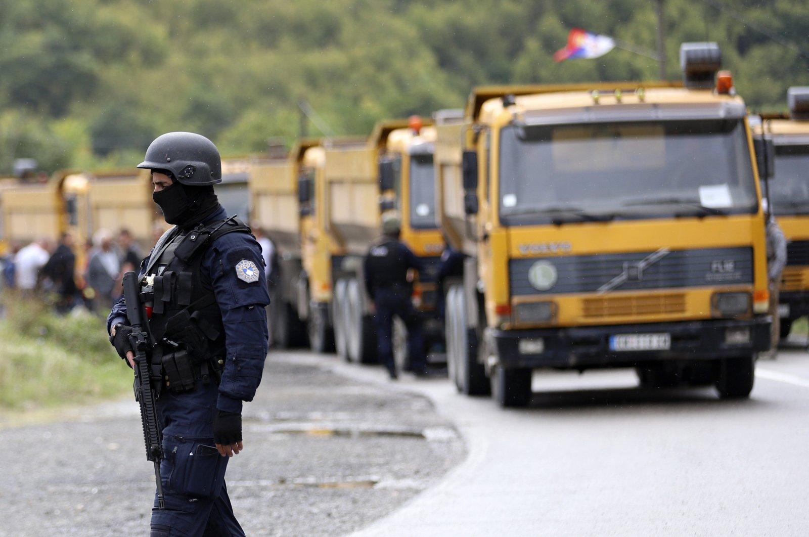 A Kosovo special police officer stands near trucks where Kosovo Serbs block a road near the northern Kosovo border crossing of Jarinje, Monday, Sept. 20, 2021. (AP Photo)