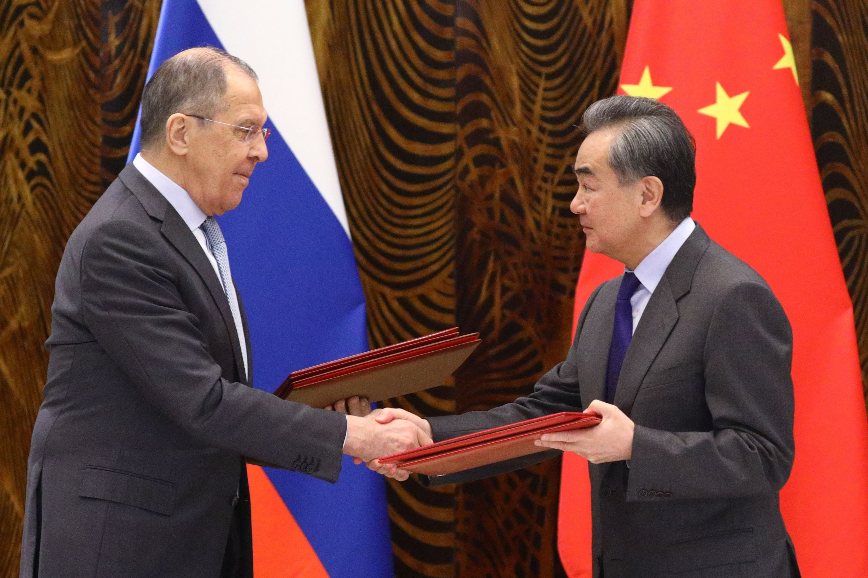 Russian Foreign Minister Sergei Lavrov (L) and Chinese Foreign Minister Wang Yi exchange documents during a signing ceremony following their talks in Guilin, China, March 23, 2021. (Russian Foreign Ministry via AFP)