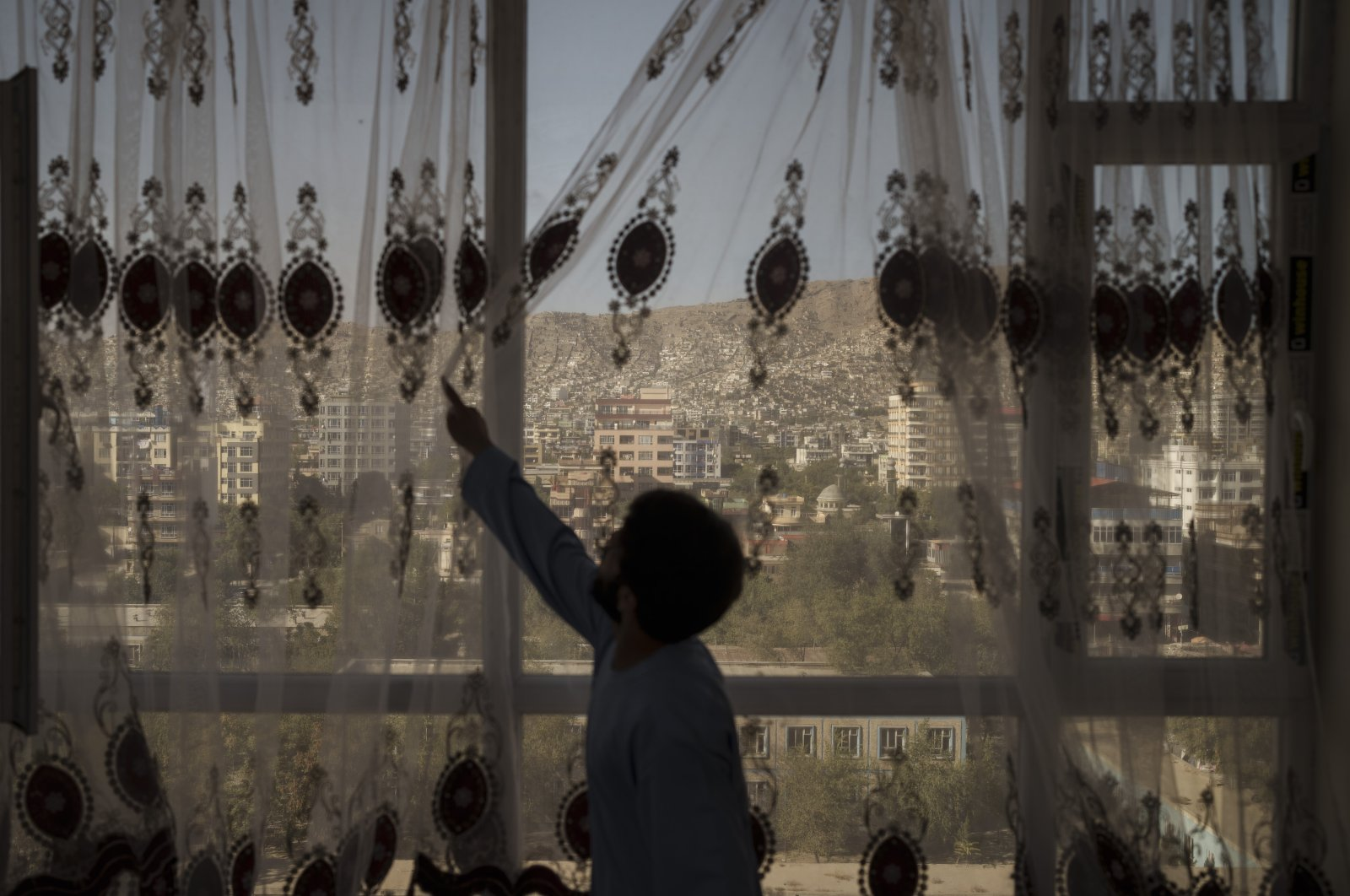 Mohammed Zakir closes the curtains of his family home, overlooking Kabul, Afghanistan, Sept. 17, 2021. (AP Photo)