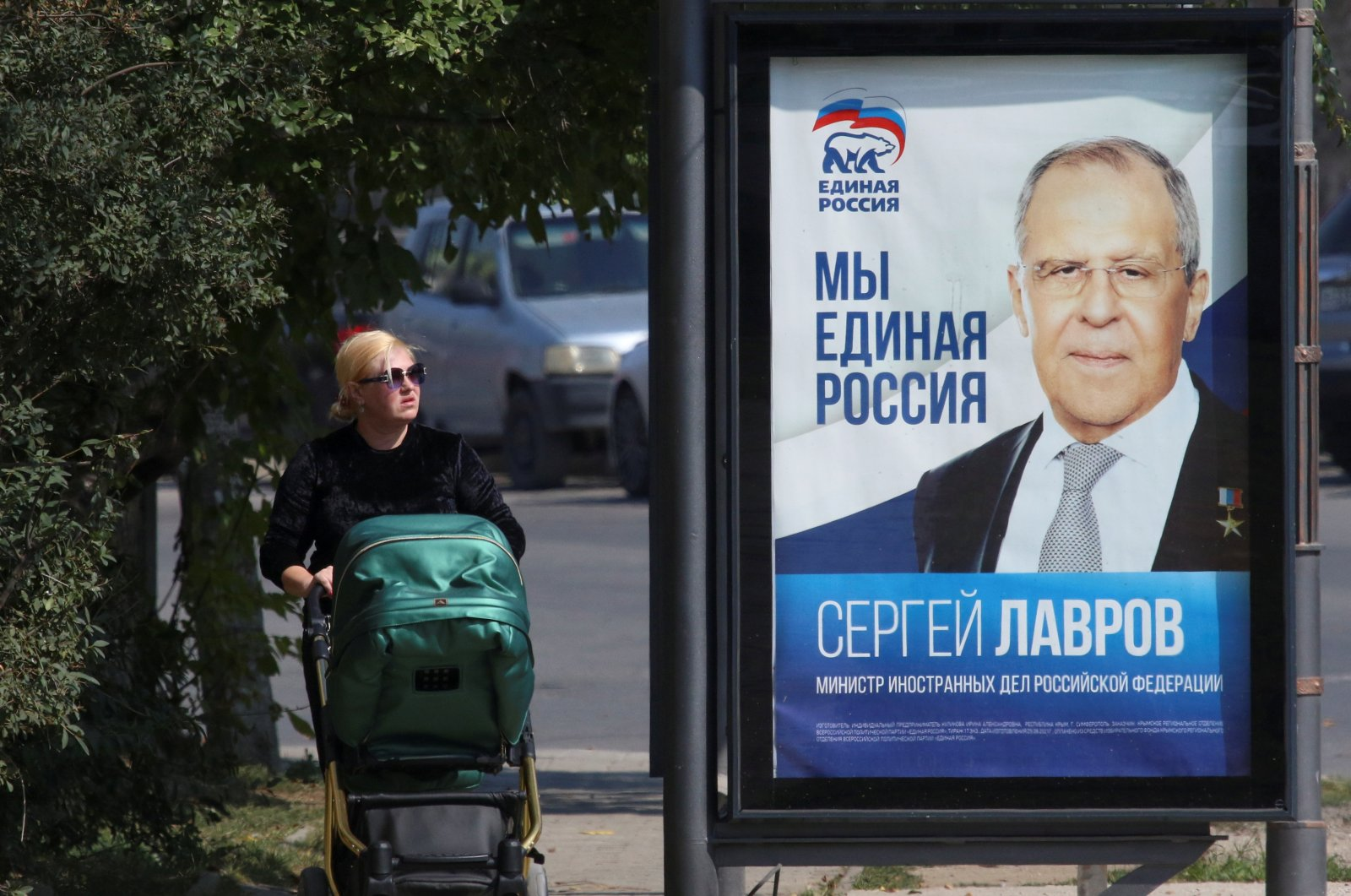 A woman walks past a campaign poster of Russian Foreign Minister Sergei Lavrov of the United Russia political party ahead of the Russian parliamentary and regional voting in Simferopol, Crimea, Sept. 15, 2021. (Alexey Pavlishak via Reuters)