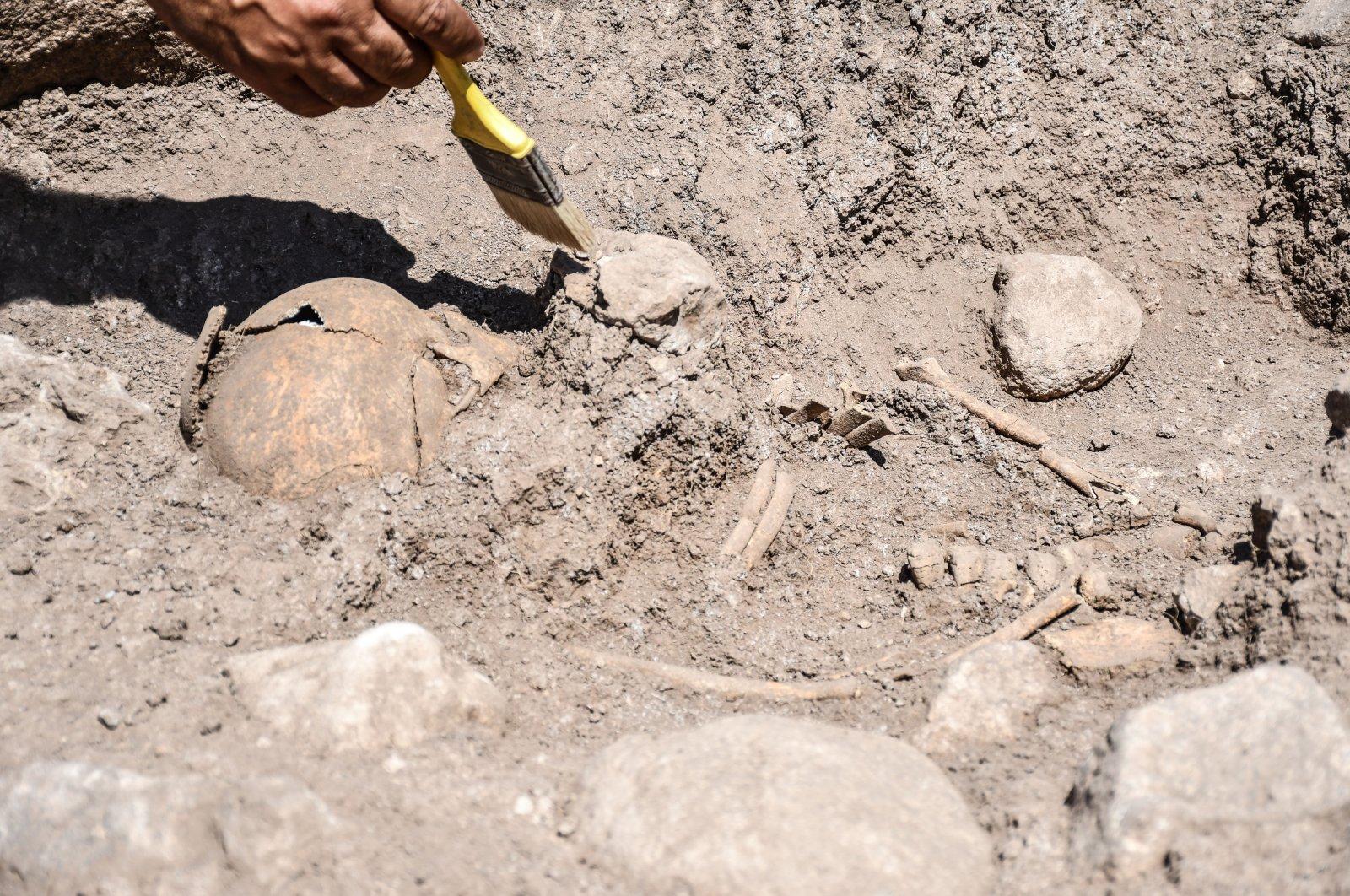 An archaeologist works on the skeleton of a child at Domuztepe Mound, Kahramanmaraş, southern Turkey, Sept. 20, 2021. (AA Photo)