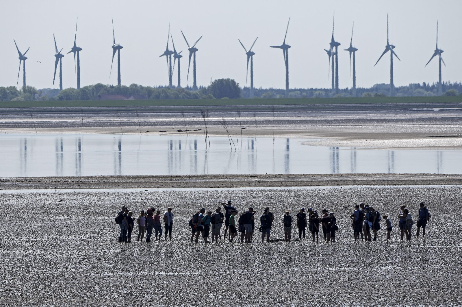People explore the Wadden Sea at the island Norderney, Germany, in front of wind turbines producing renewable energy, June 1, 2021. (AP File Photo)