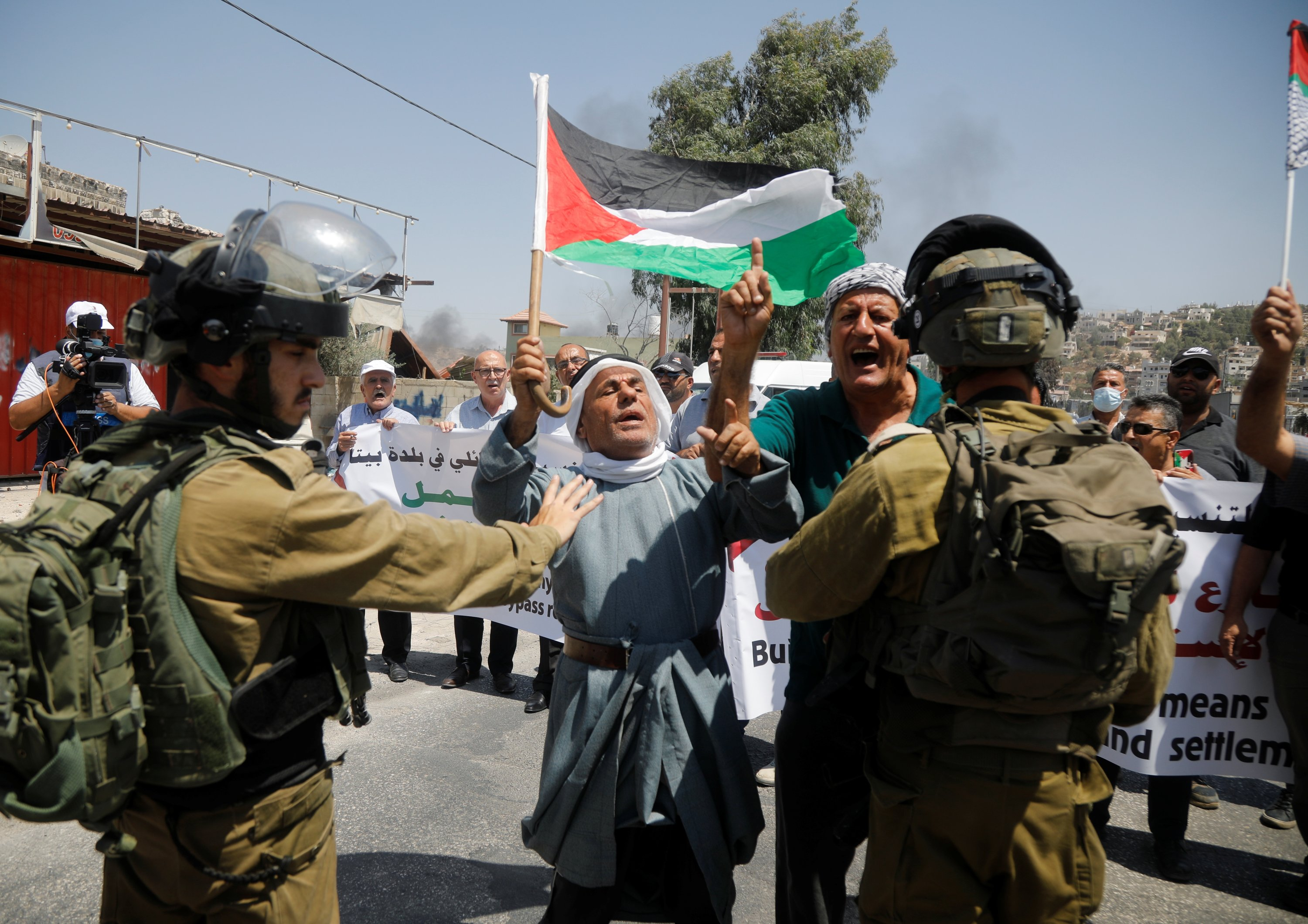 A Palestinian protester waves the flag of Palestine as Israeli soldiers stand guard during a protest against Israeli settlements in Beita, in the Israeli-occupied West Bank, August 25, 2021 (Raneen Sawafta / Reuters)