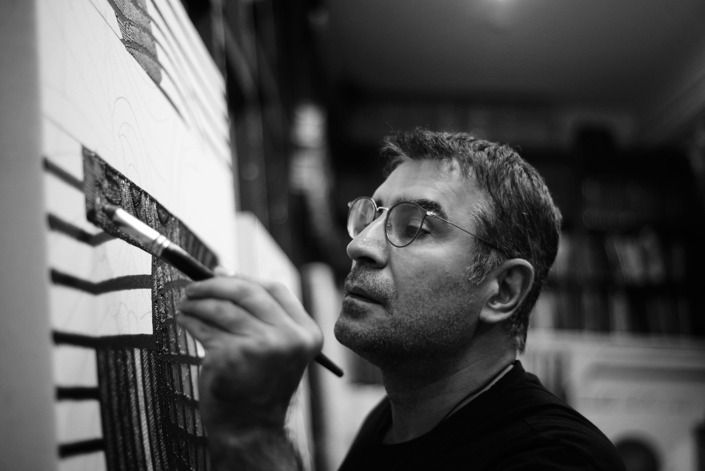 Ahmet Güneştekin paints a work.