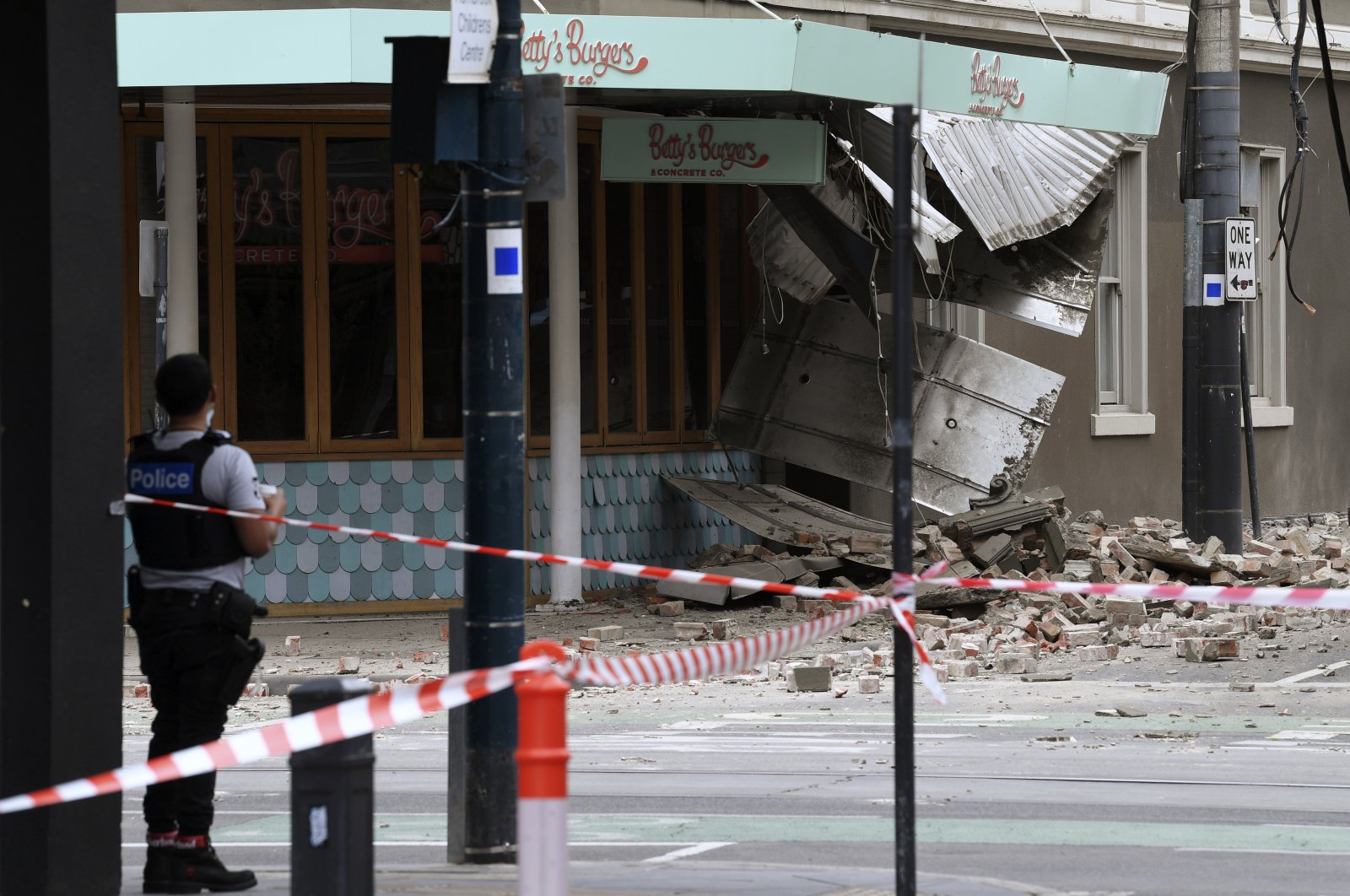 A police officer closes an intersection where debris is scattered in the road after an earthquake damaged a building in Melbourne, Australia, Sept. 22, 2021. (AAP Image via AP)