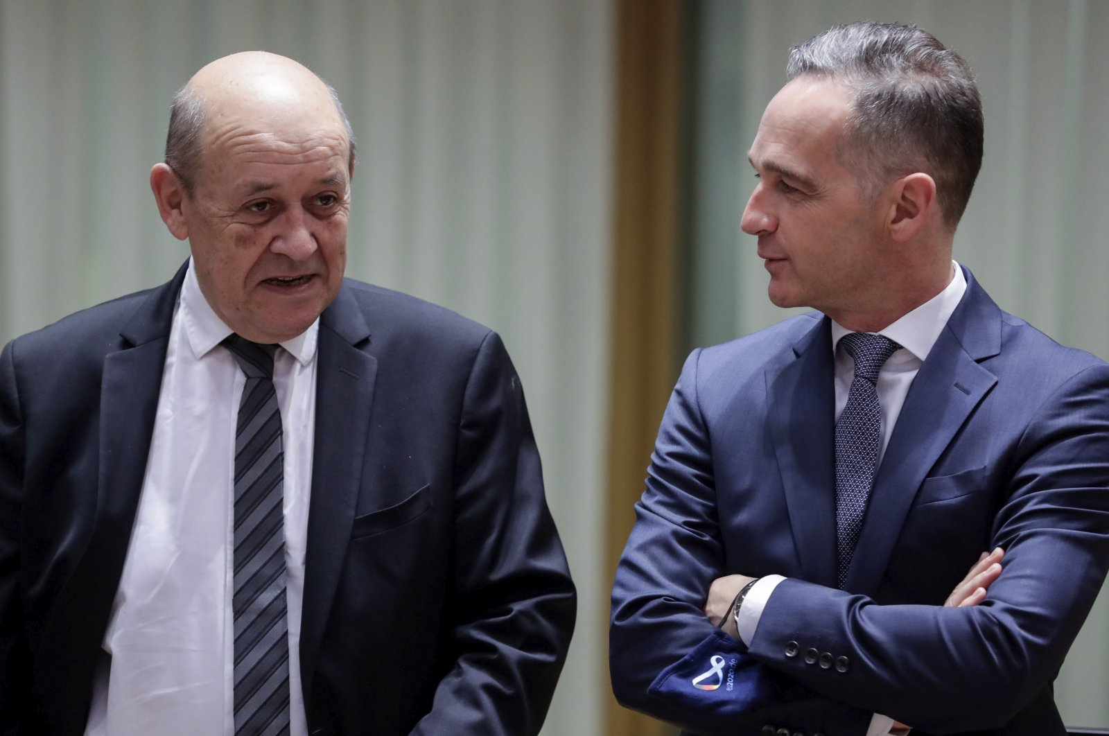 French Foreign Minister Jean-Yves Le Drian (L) speaks with German Foreign Minister Heiko Maas during a meeting of EU foreign ministers at the European Council building in Brussels, July 13, 2020. (Pool Photo via AP)