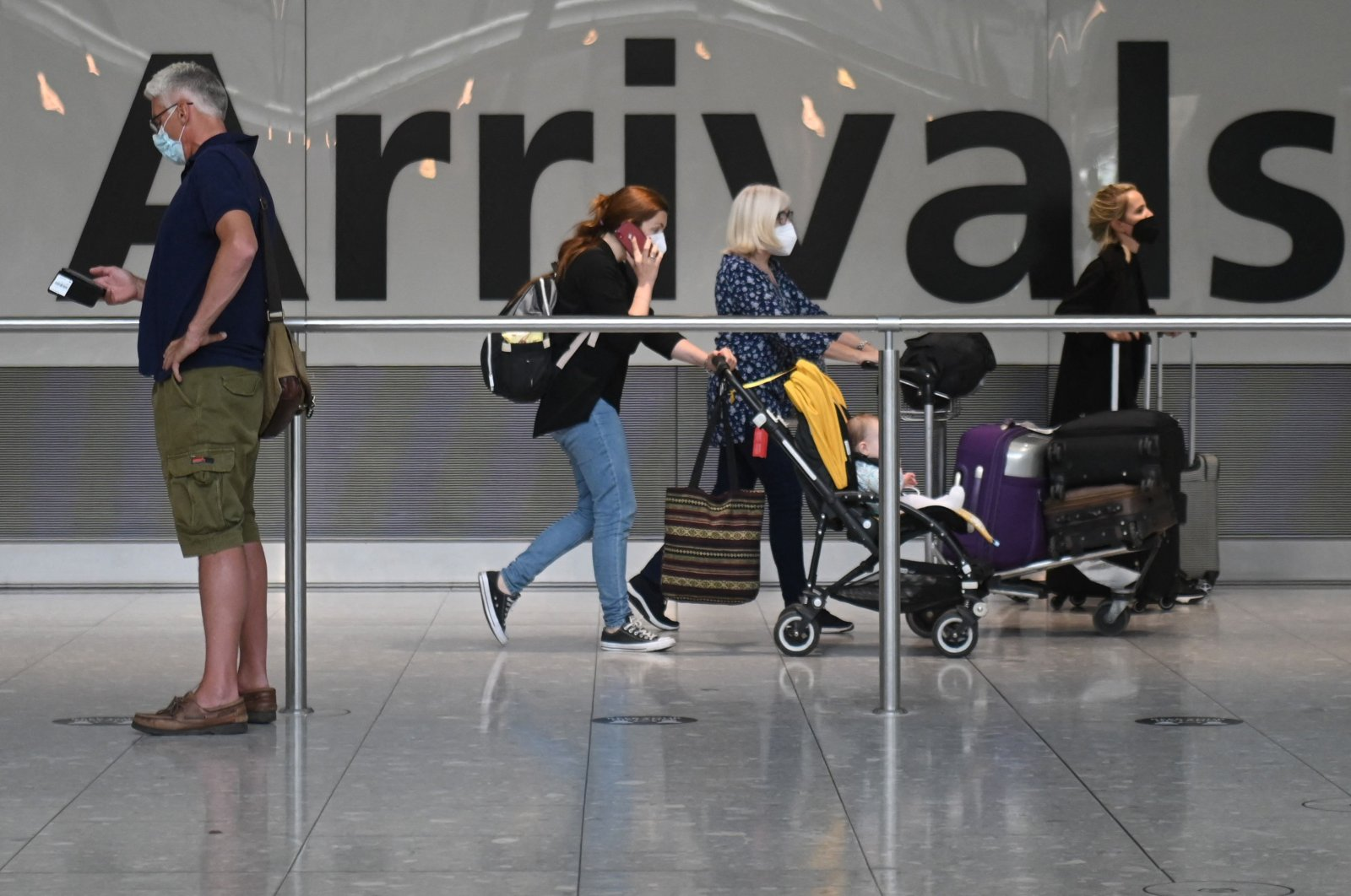Passengers push their luggage after arrival to Terminal 5 at Heathrow Airport in London, U.K., June 3, 2021. (AFP Photo)