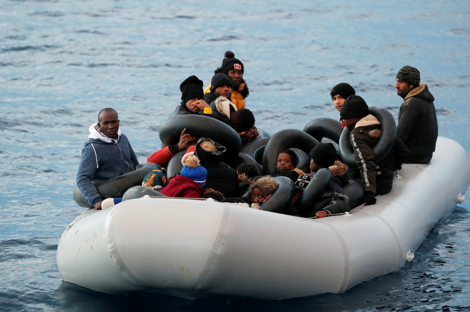 Migrants are seen on a dinghy following a failed attempt to cross to the Greek island of Lesbos, as a Turkish coast guard boat approaches them, on the waters of the North Aegean Sea, off the shores of Çanakkale, Turkey, March 6, 2020. (Reuters File Photo)