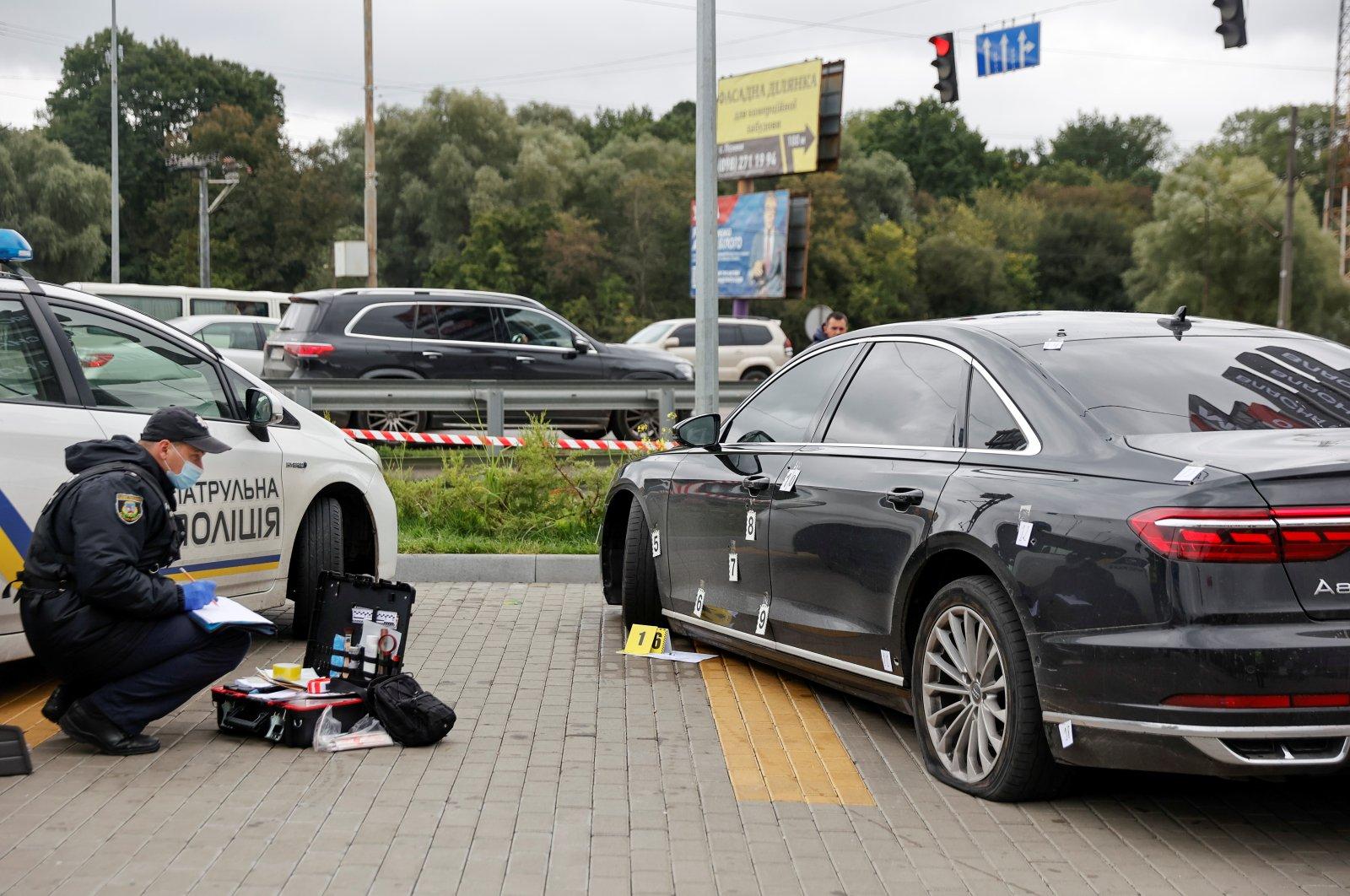 An investigator examines bullet holes in a car of Serhiy Shefir, Ukrainian President Volodymyr Zelenskyy's principal aide, following an assault outside the capital Kyiv, Ukraine September 22, 2021. (Reuters Photo)