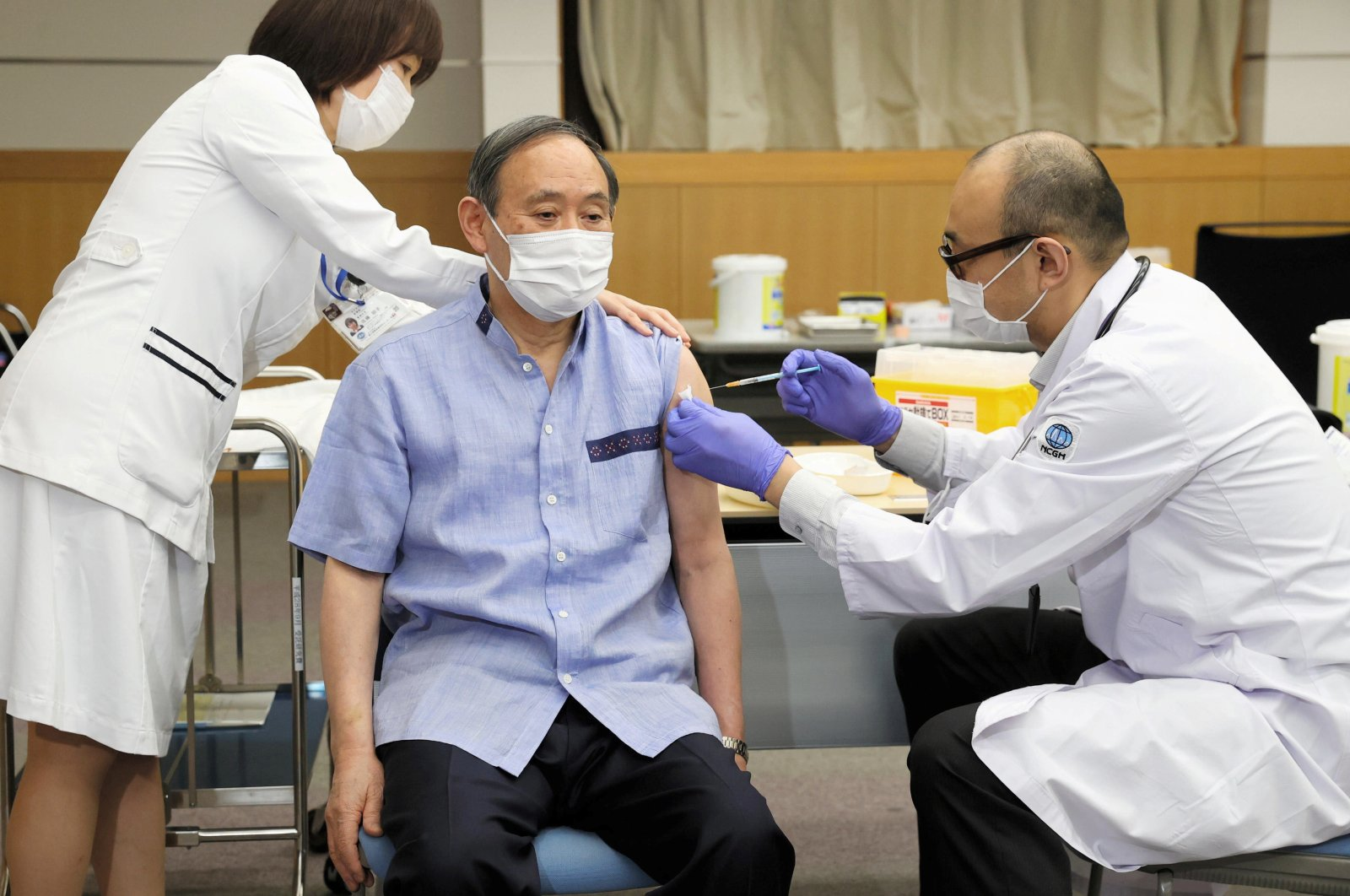 Japan's Prime Minister Yoshihide Suga receives his first dose of the Pfizer-BioNTech coronavirus vaccine at the National Center for Global Health and Medicine in Tokyo, Japan March 16, 2021. (Kyodo via REUTERS)