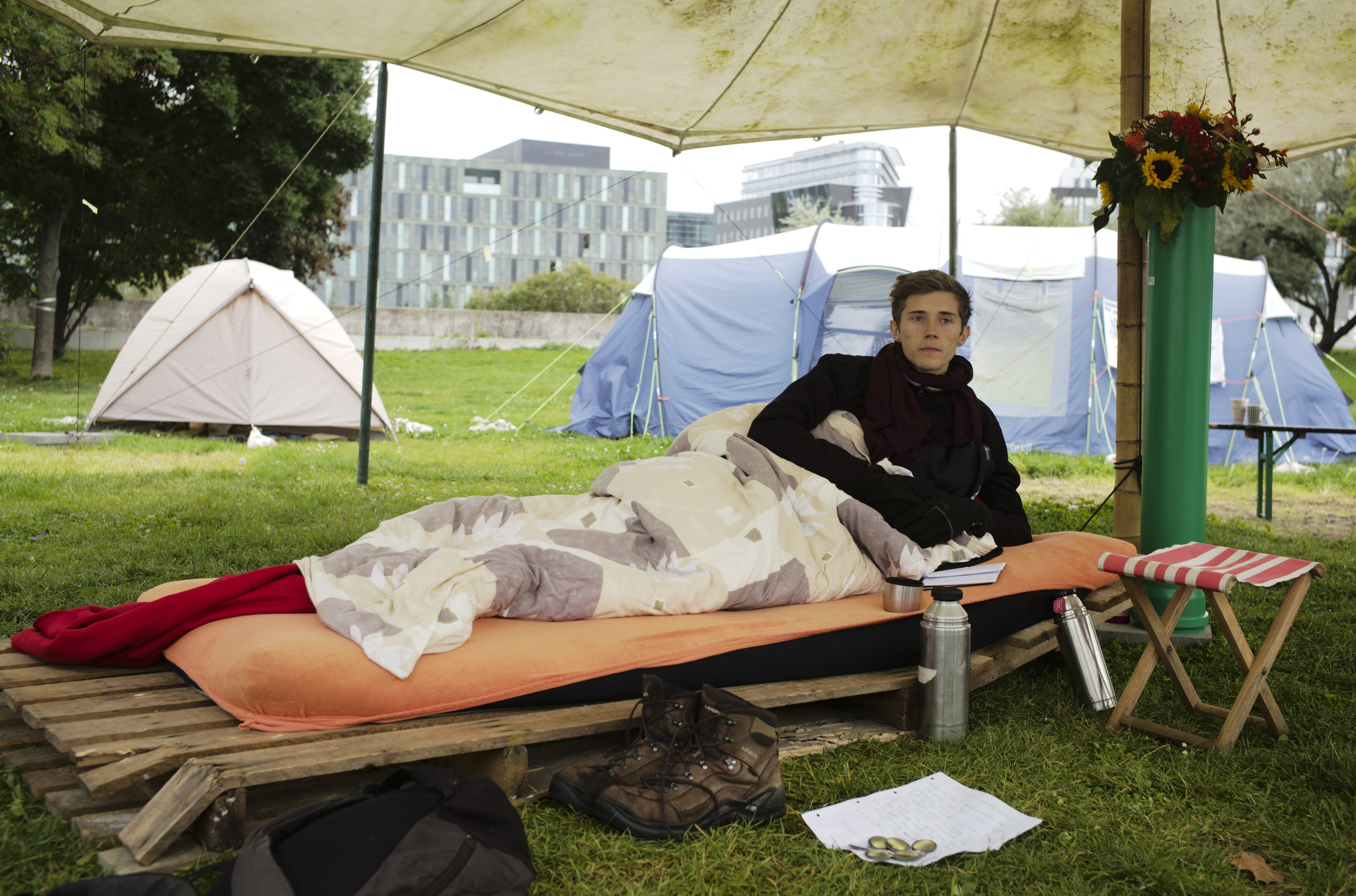 Climate activist Henning Jeschke, who has spent 24 days on a hunger strike, lays on a mattress under a tent in a small camp of climate activists as he poses for a photo in Berlin, Germany, Sept. 22, 2021. (AP Photo)