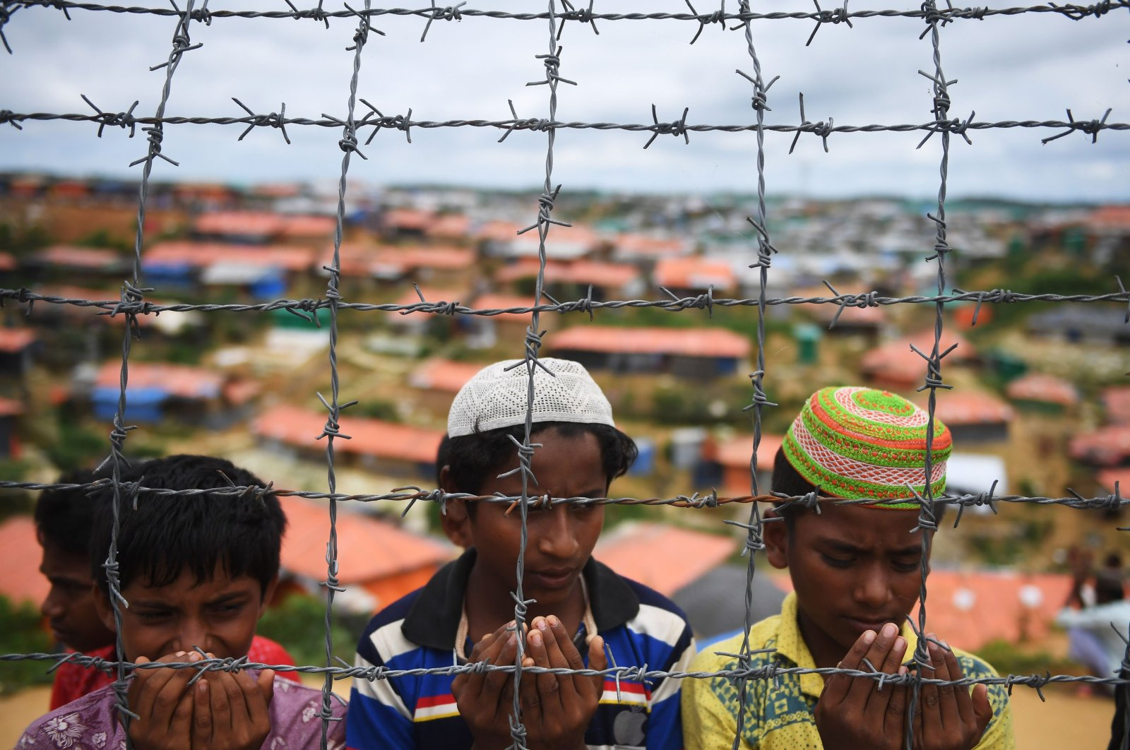 Rohingya refugees perform prayers as they attend a ceremony organized to remember the first anniversary of a military crackdown that prompted a massive exodus of people from Myanmar to Bangladesh, at the Kutupalong refugee camp in Ukhia, Cox's Bazar, Bangladesh, Aug. 25, 2018. (AFP Photo)