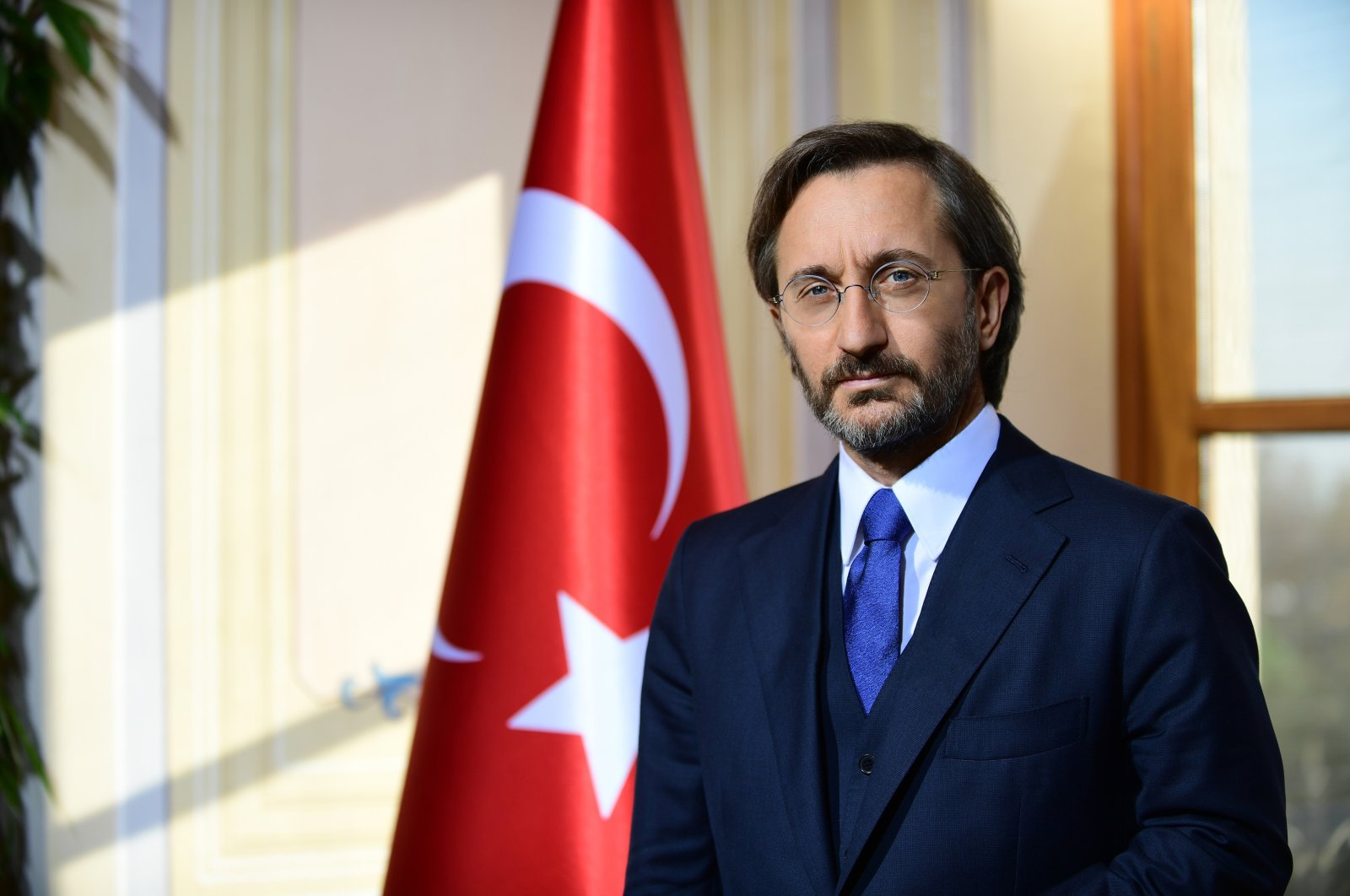 Presidential Communications Director Fahrettin Altun poses near a Turkish flag in this undated file photo. (IHA File Photo)
