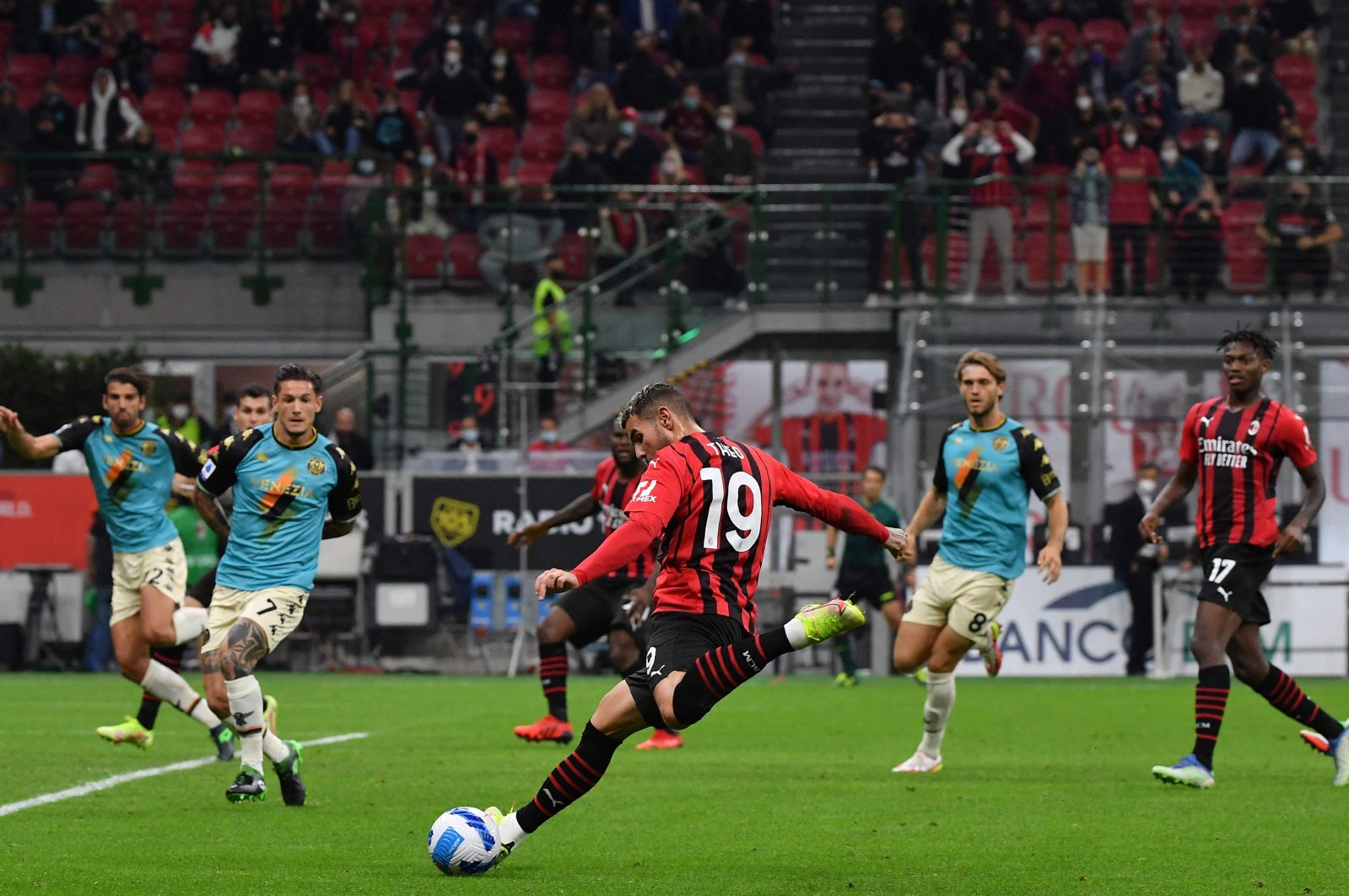 AC Milan's French defender Theo Hernandez (C) shoots to score during a Serie A match against Venezia at the San Siro, Milan, Italy, Sept. 22, 2021. (AFP Photo)