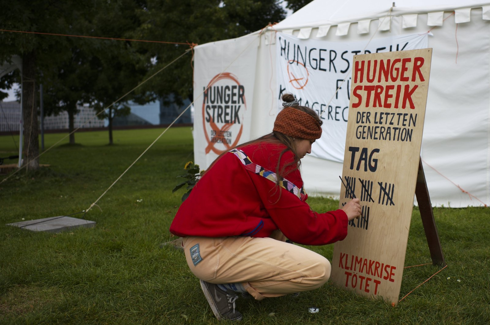 Climate activist Carla Hinrichs makes a line on a wooden board to count the days a small camp of climate activists have been in a hunger strike, near the chancellery in Berlin, Germany, Sept. 22, 2021. (AP Photo)