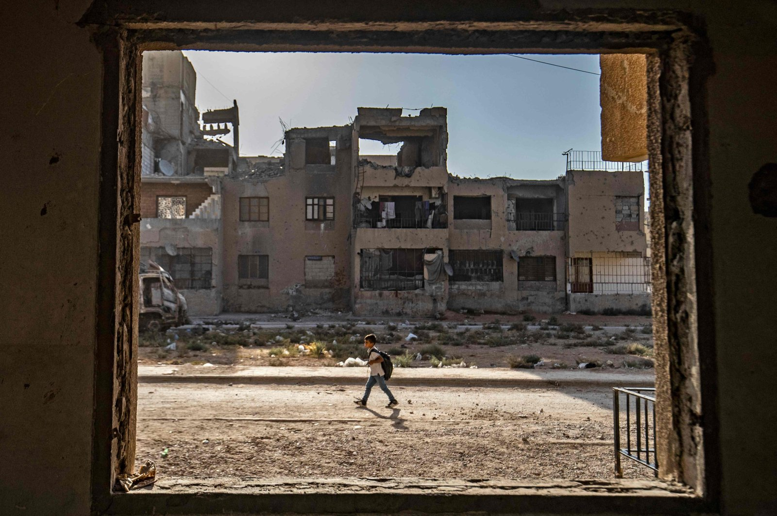 A Syrian student walks to school past damaged buildings in the northern city of Raqqa, Syria, Sept. 23, 2021. (AFP Photo)