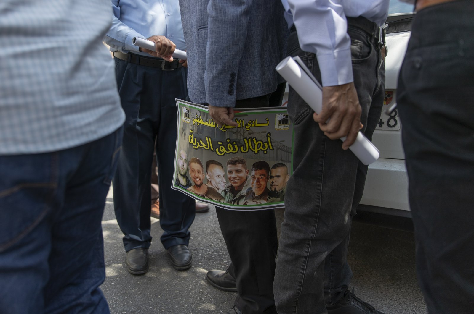 """A Palestinian man carries a poster with pictures of the six Palestinian prisoners who escaped from an Israeli jail that says """"heroes of the freedom tunnel,"""" during a protest supporting prisoners, in the occupied West Bank city of Ramallah, Palestine, Sept. 14, 2021. (AP Photo)"""