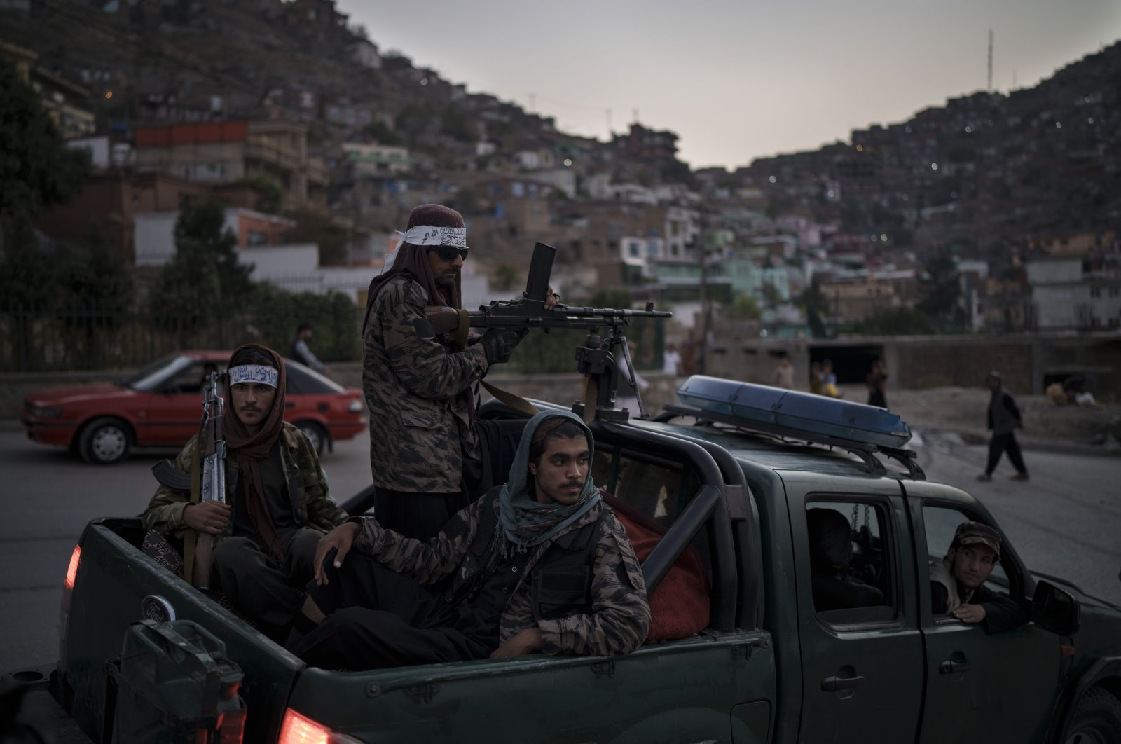 Taliban fighters sit on the back of a pickup truck as they stop on a hillside in Kabul, Afghanistan, Sept. 19, 2021. (AP Photo)